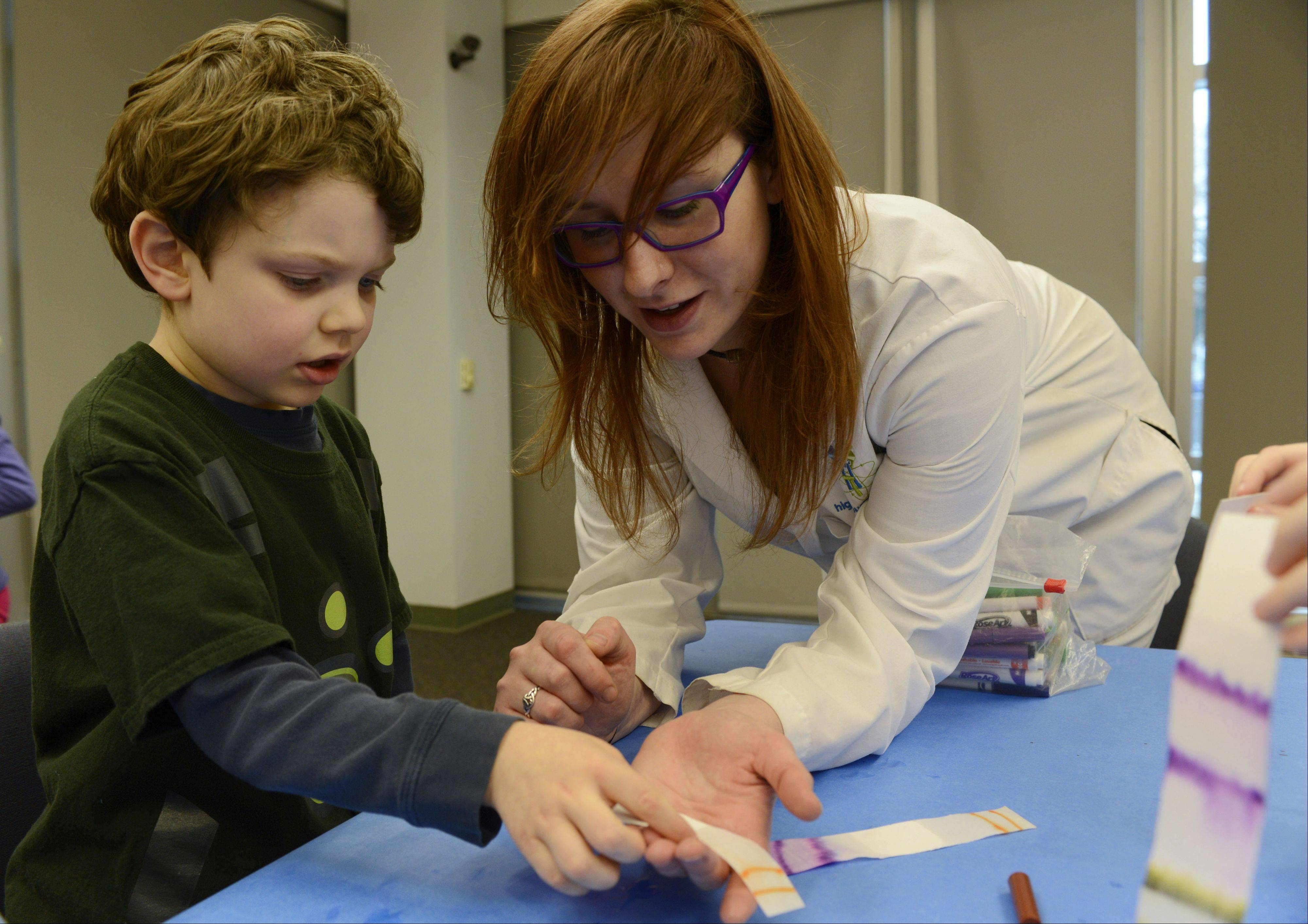 JOE LEWNARD/jlewnard@dailyherald.com Collin Narens, 6, of Wheeling learns about chromatography and capillary action from Jenn Biela during a �Chemistry Fun� program Saturday at the Indian Trails Library District in Wheeling.