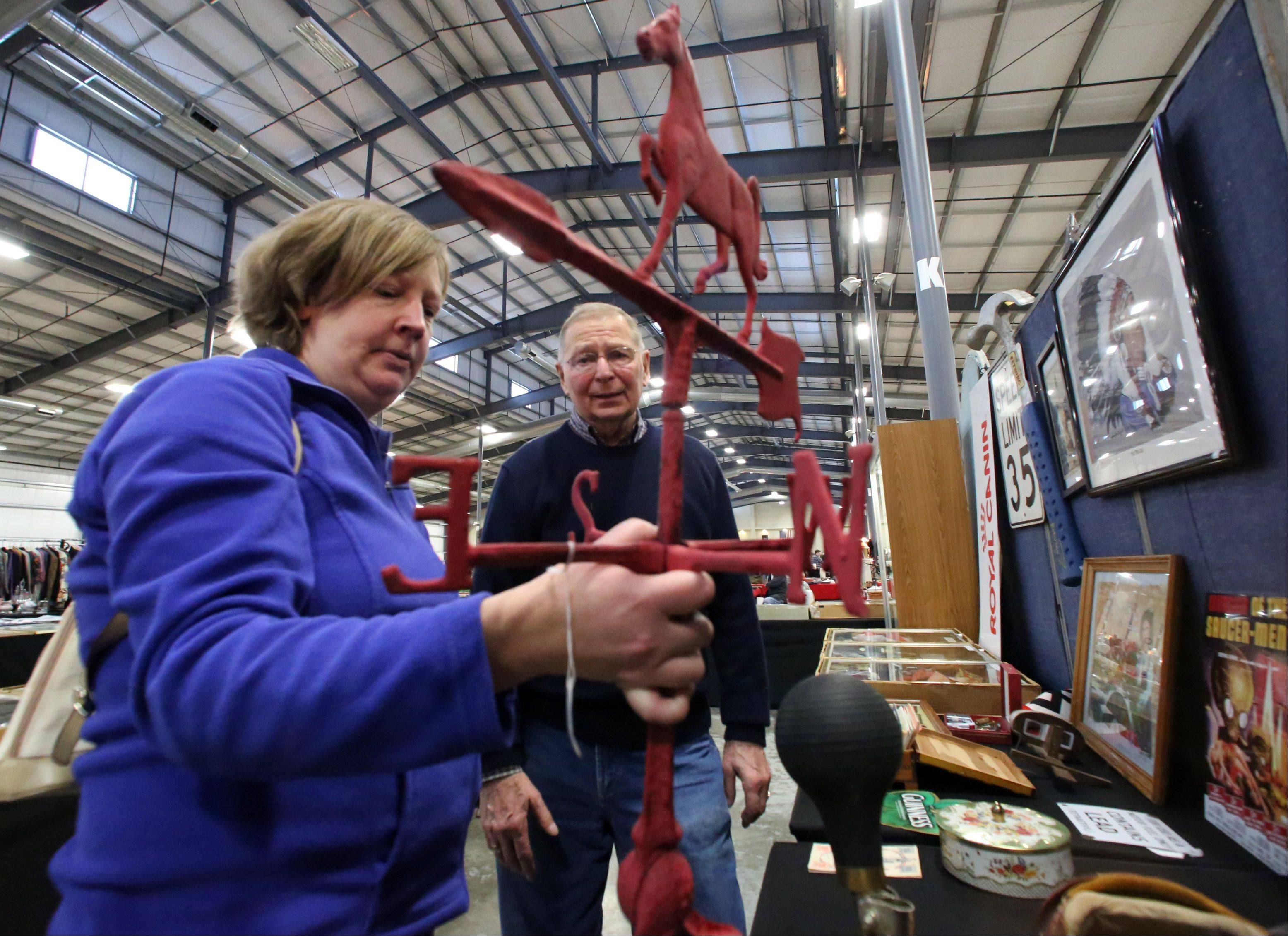 Julie Harding of Libertyville purchases a 1915 weather vane that was used at a Wisconsin farm from Bob Potasnik of Bonduel, Wis., at Zurko Antiques and Flea Market on Saturday at Lake County Fairgrounds in Grayslake.