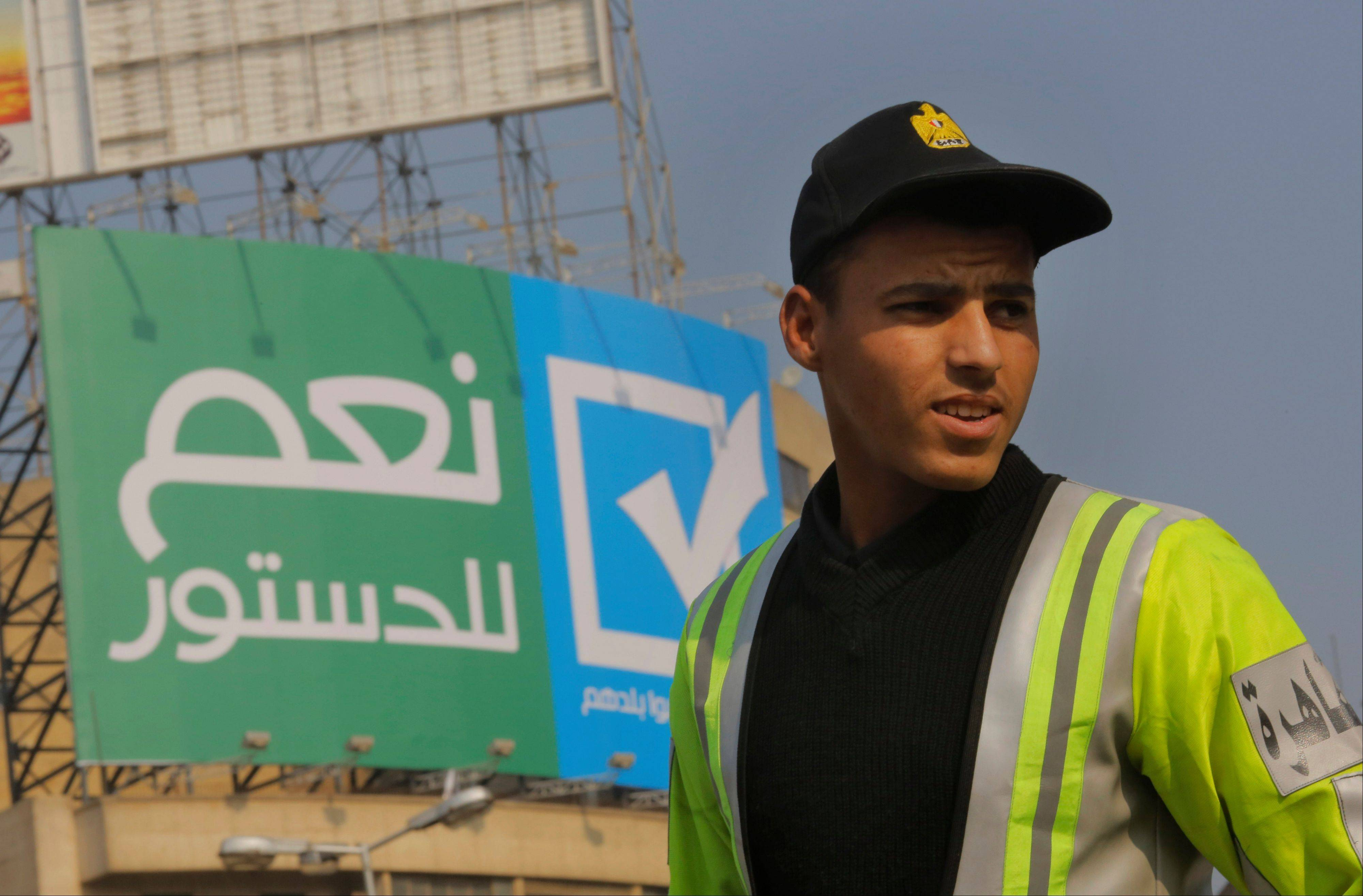 An Egyptian traffic policeman stands under a billboard Saturday with Arabic that reads, �yes to the constitution, Egyptians love their country,� in Tahrir Square, Cairo.