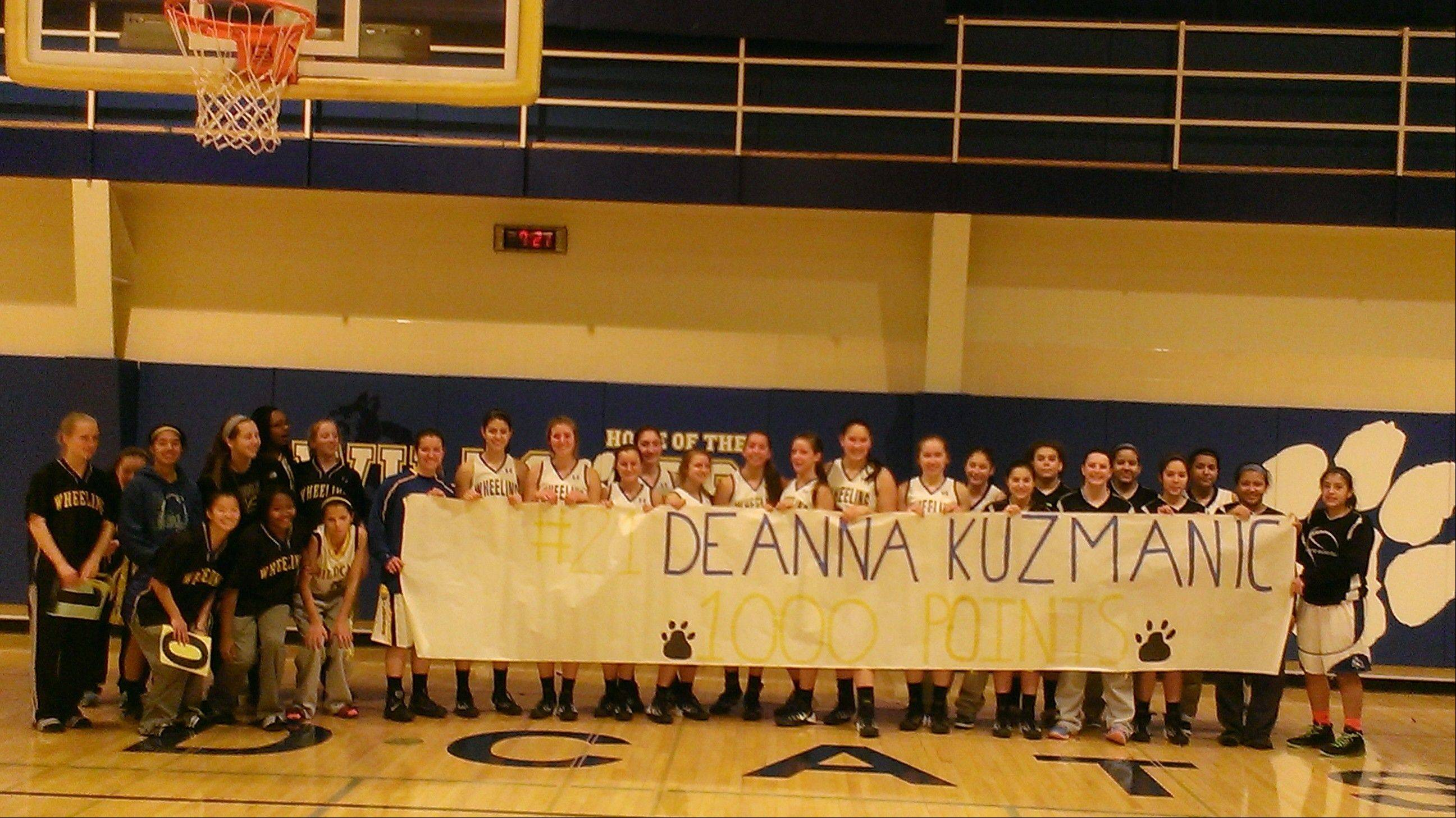 Wheeling salutes junior Deanna Kuzmanic after she surpassed 1,000 career points in Mid-Suburban League play Saturday in a victory over Elk Grove.