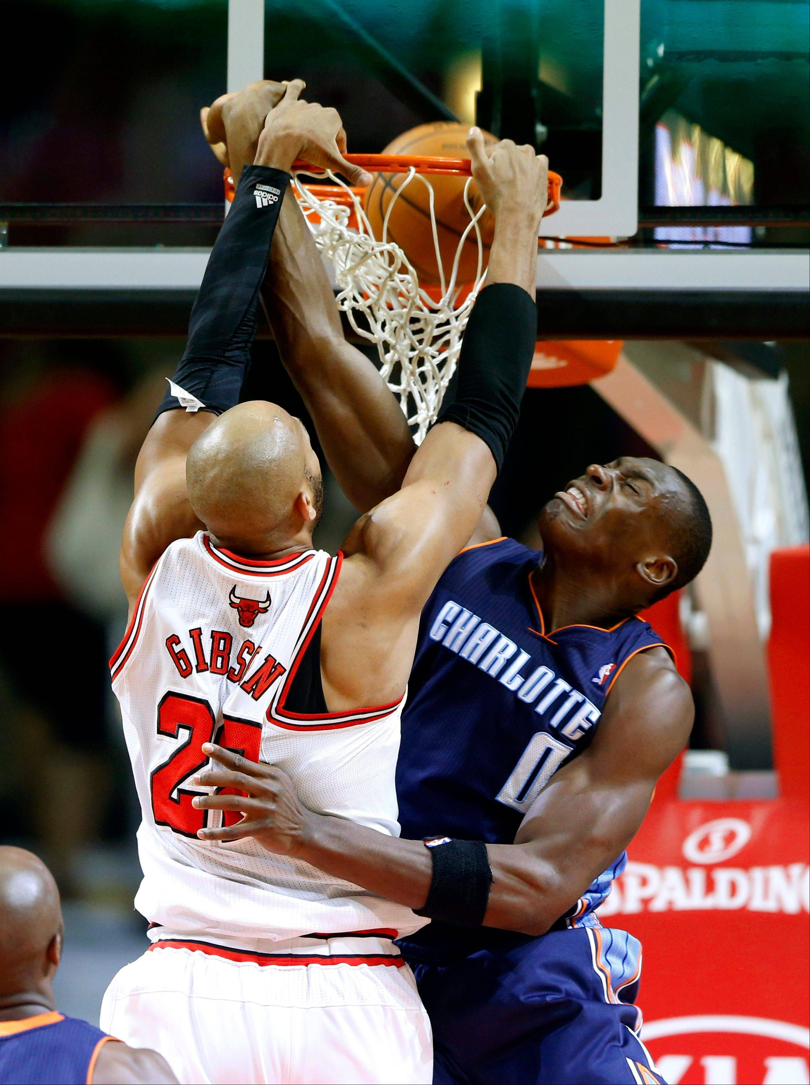 The Bulls' Taj Gibson delivers a power slam against the Bobcats' Bismack Biyombo on Saturday at the United Center.