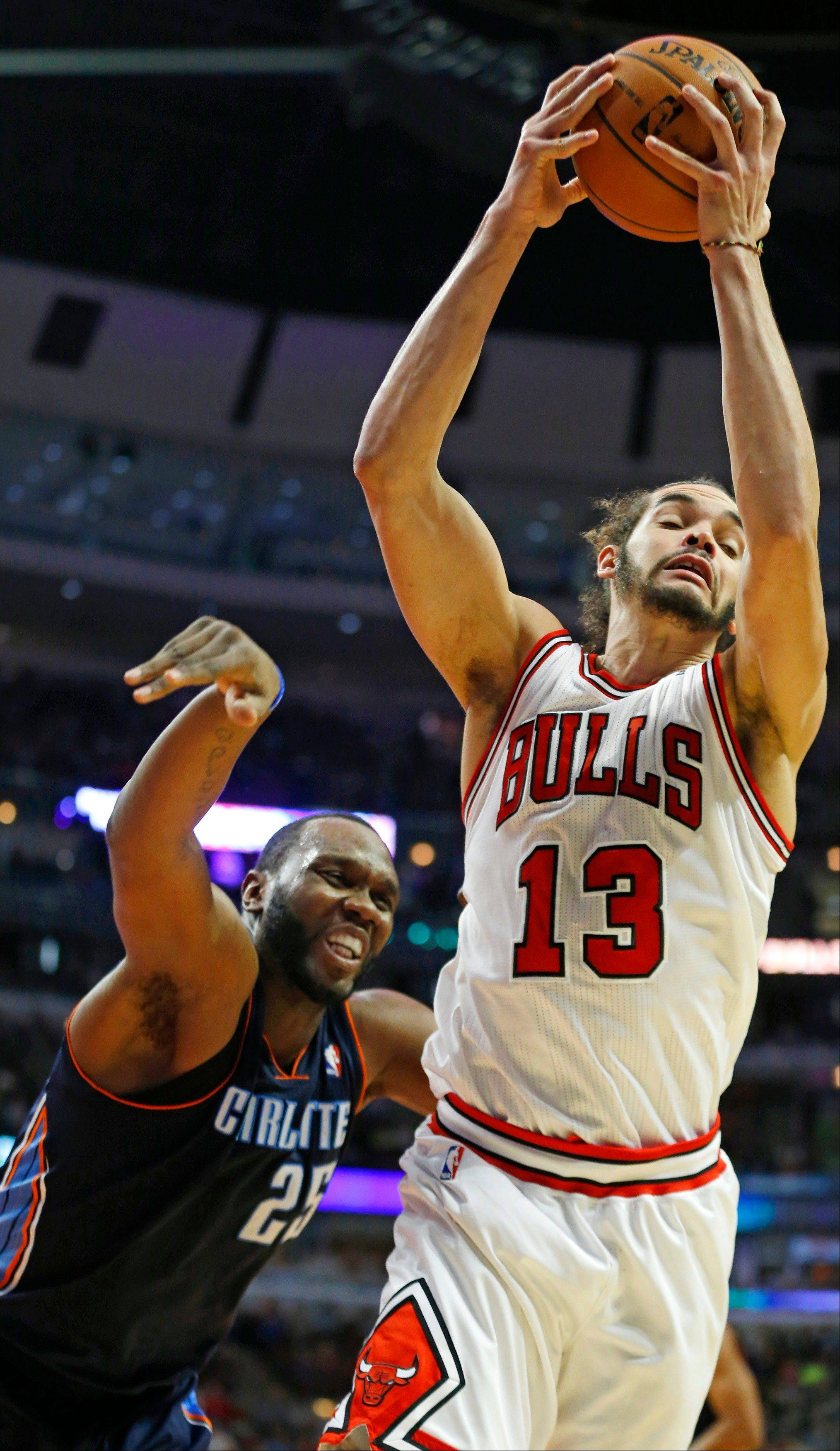 Chicago Bulls center Joakim Noah (13) rebounds the ball away from Charlotte Bobcats center Al Jefferson (25) Saturday night at the United Center. The Bulls won 103-97.