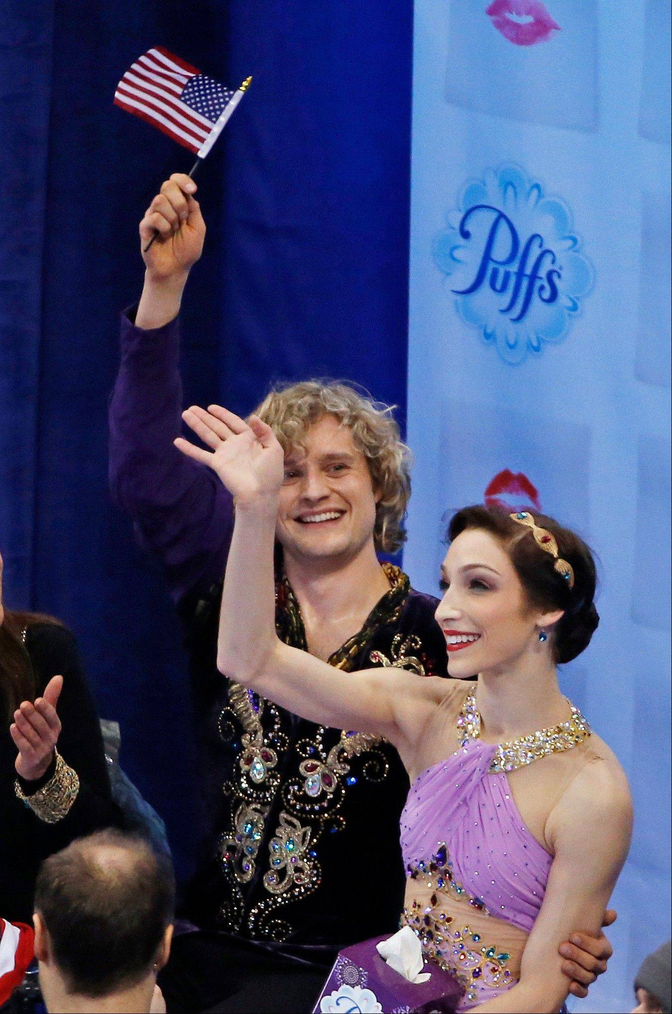 Meryl Davis and Charlie White wave as scores are posted after skating in the ice dance free skate at the U.S. Figure Skating Championships Saturday in Boston.