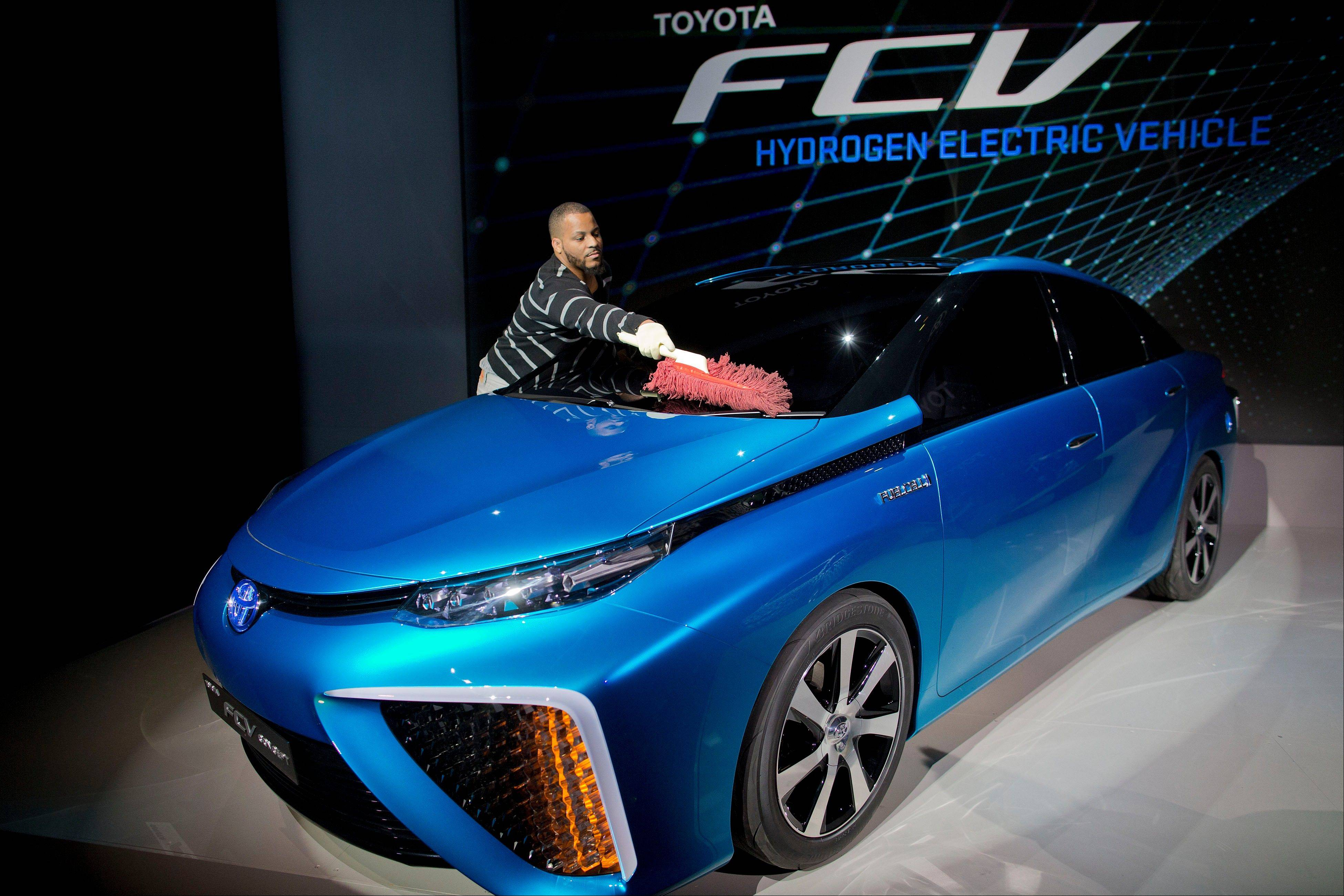 A production crew member dusts off Toyota's FCV hydrogen electric concept car during the International Consumer Electronics Show in Las Vegas. Toyota announced the car would be available to consumers in 2015.