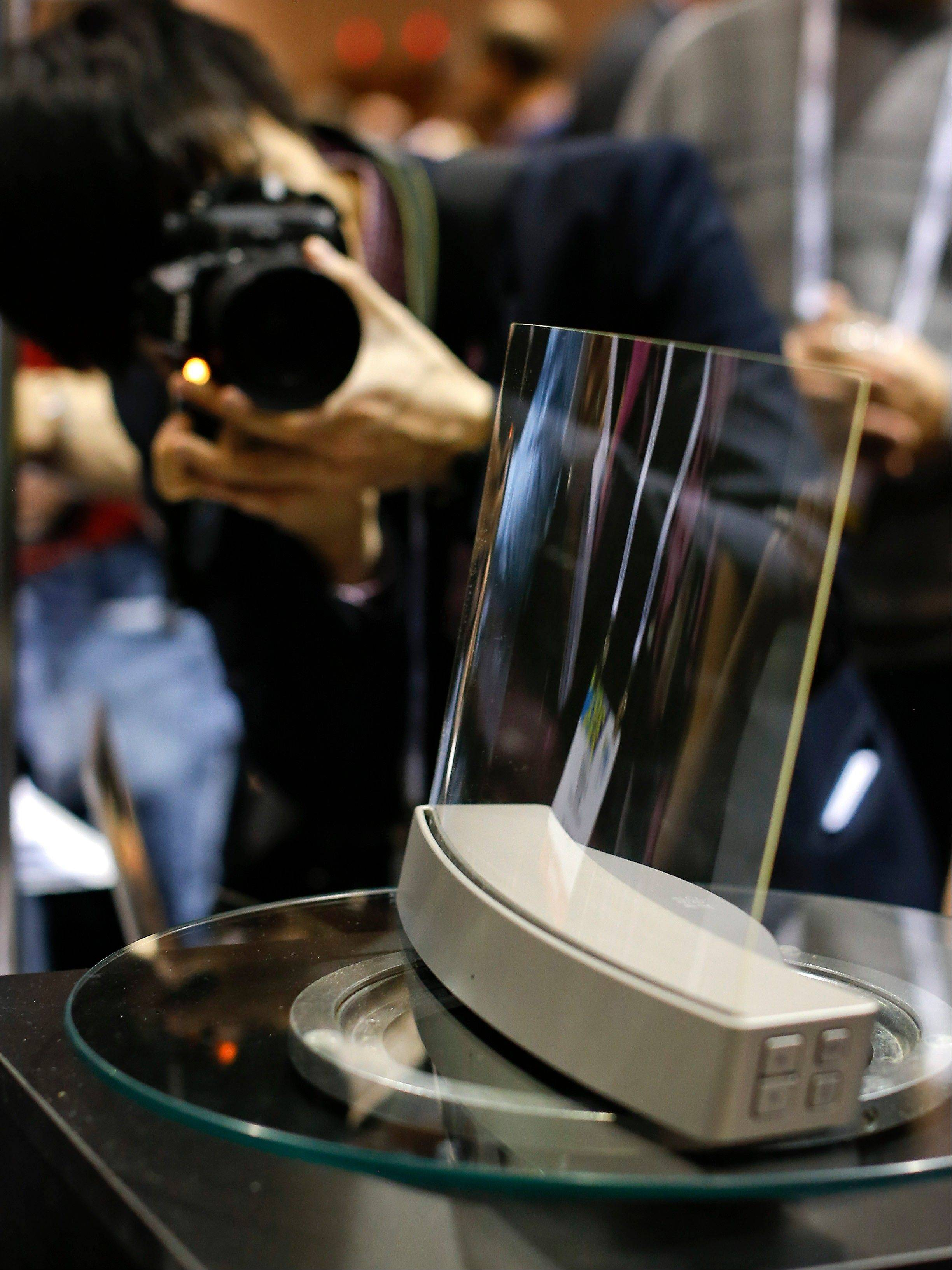 Members of the media photograph a glass speaker called Clio during the International Consumer Electronics Show in Las Vegas. The speaker, produced by ClearView Audio uses a single piece of curved millimeter-thick acrylic glass that sits on a dock which vibrates it in a finely tuned way so that it can play music. It works with Bluetooth streaming and with a 3.5 millimeter jack.