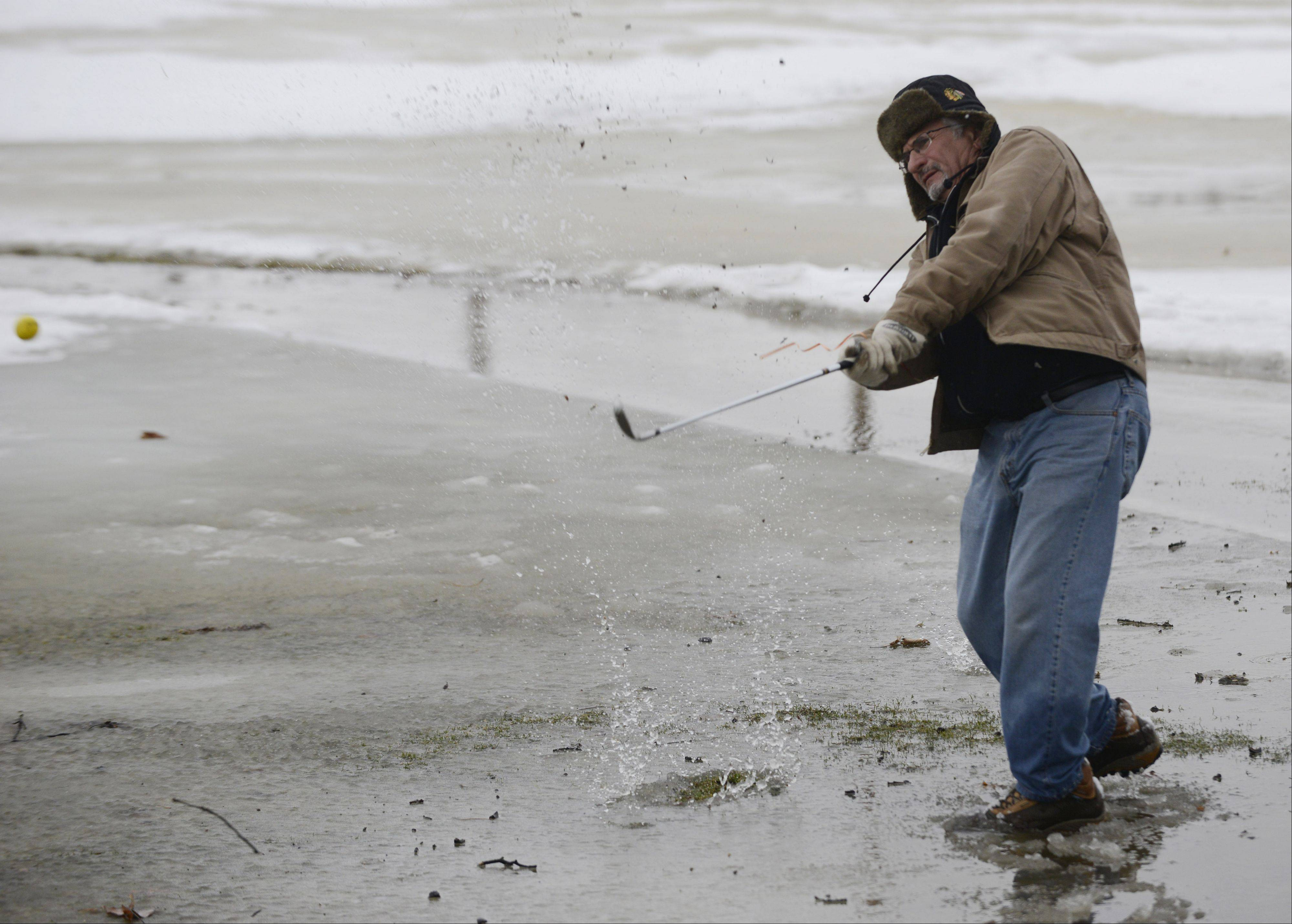 Paul Scaglione of Mount Prospect hits his ball from a puddle of melted snow Saturday during the Chili Open at the Golf Center in Des Plaines.