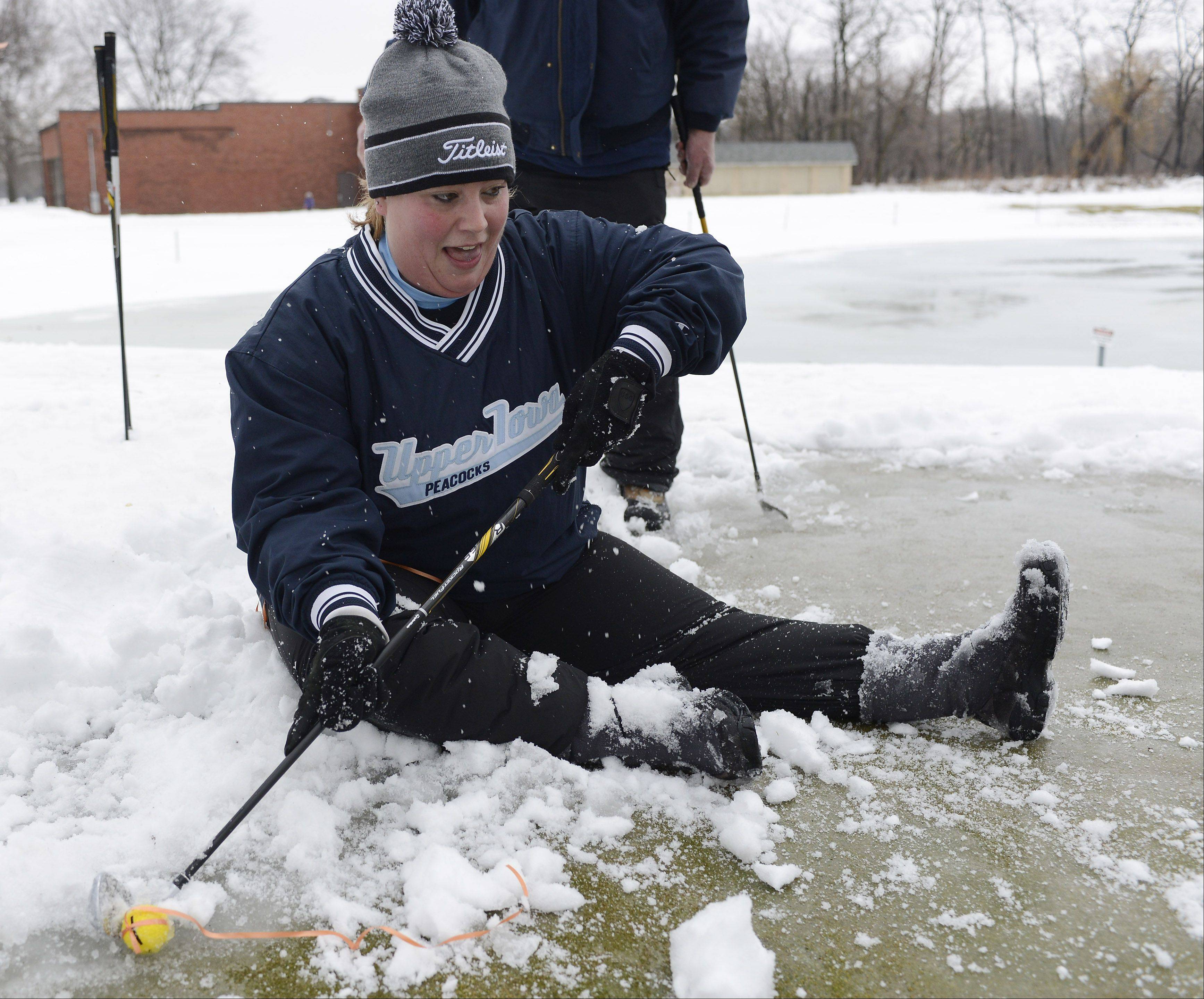 Jessica Lang of Mount Prospect, who got the lowest female score, tries to make her putt from a seated position after slipping on the icy green Saturday during the Chili Open at the Golf Center in Des Plaines.