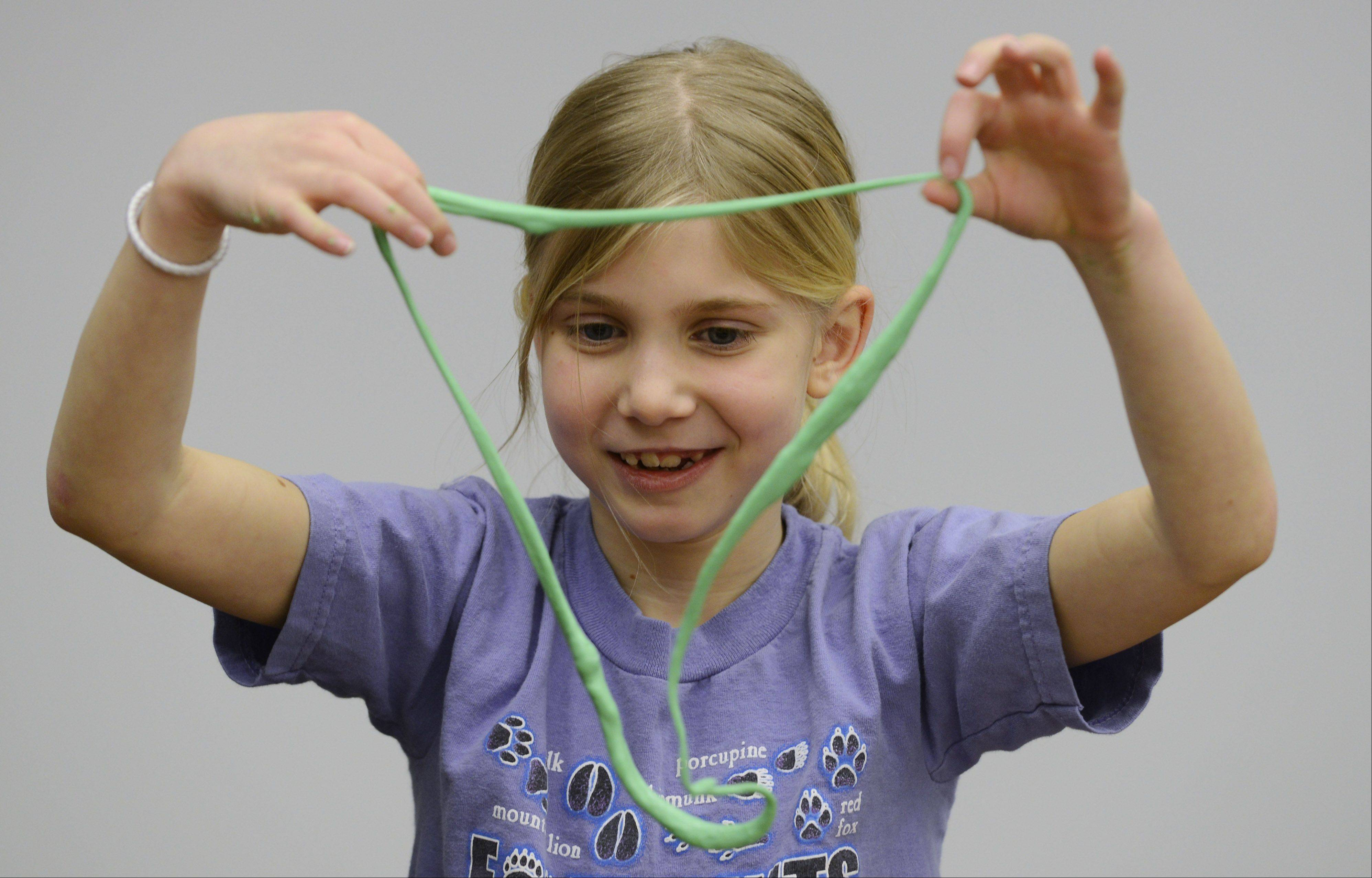 "JOE LEWNARD/jlewnard@dailyherald.comSara Thomas, 8, of Buffalo Grove creates a necklace from the silly putty she made during a ""Chemistry Fun"" program Saturday at the Indian Trails Library District in Wheeling."