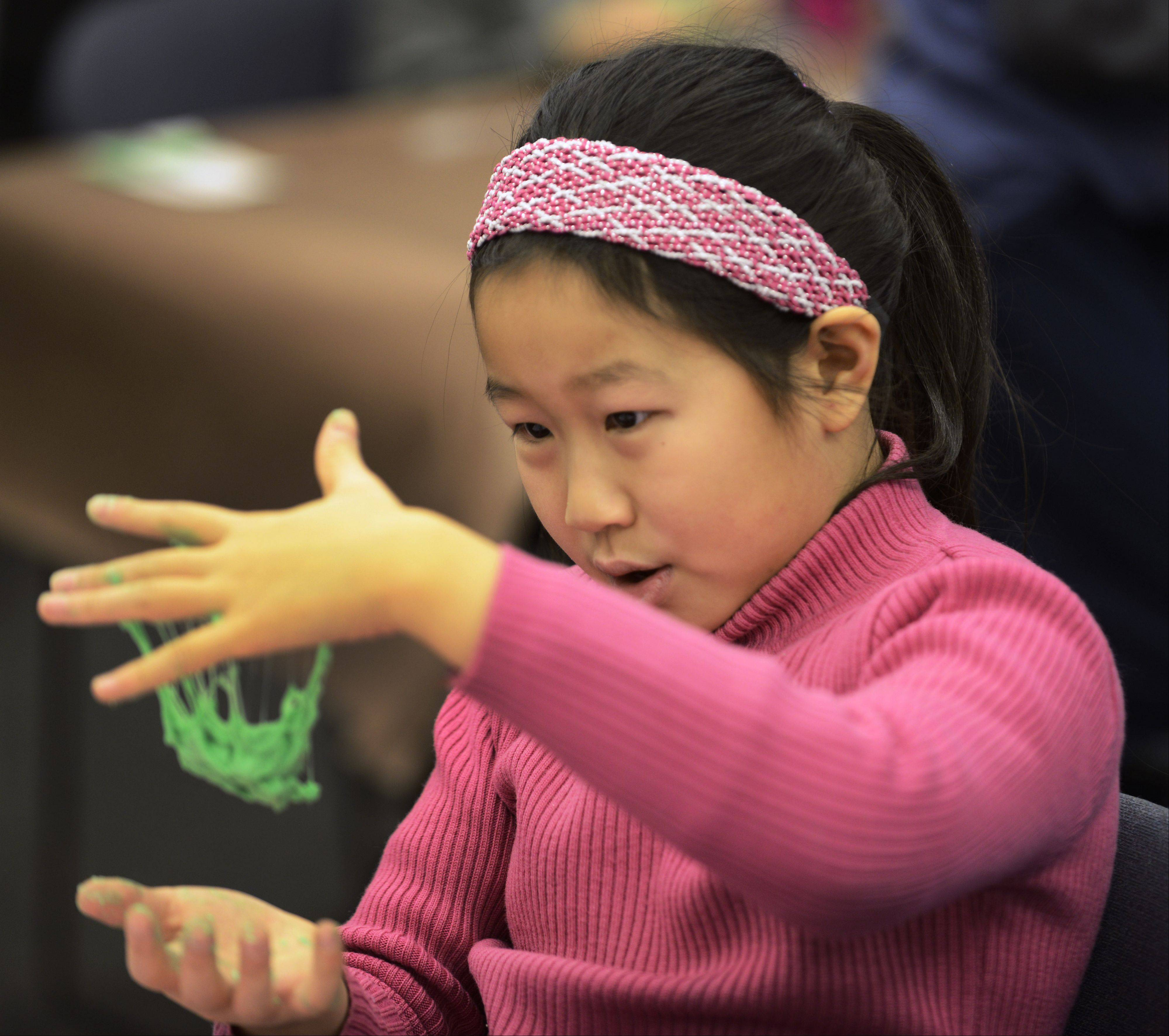 "JOE LEWNARD/jlewnard@dailyherald.comCindy Ho, 9, of Buffalo Grove makes silly putty from a mixture of borax, water, food coloring and glue during a ""Chemistry Fun"" program Saturday at the Indian Trails Library District in Wheeling."