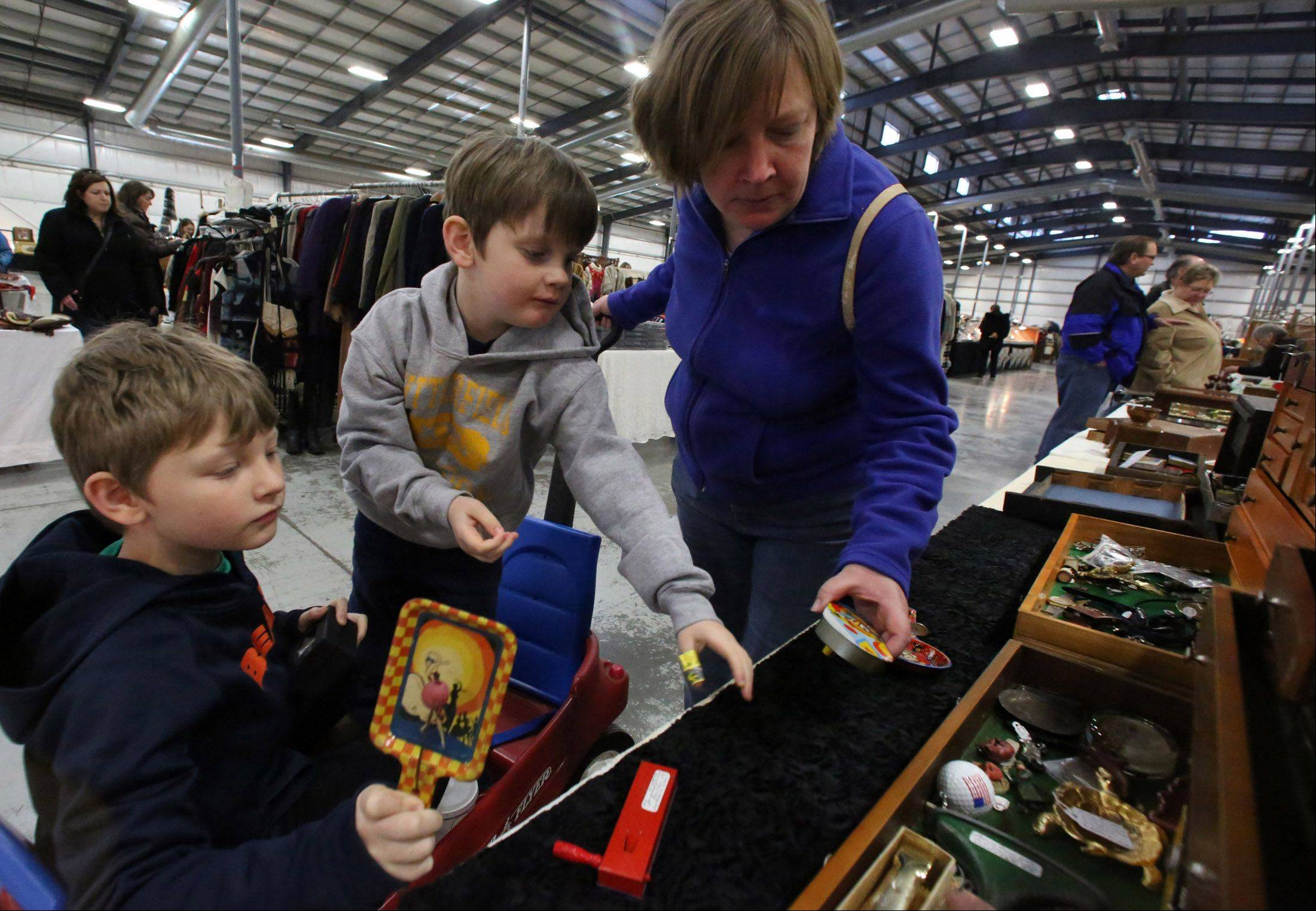 Julie Harding of Libertyville looks at old-fashioned noise makers with her sons Alexander, 7, left, and Nathaniel, 6, at Zurko Antiques and Flea Market on Saturday at Lake County Fairgrounds in Grayslake.