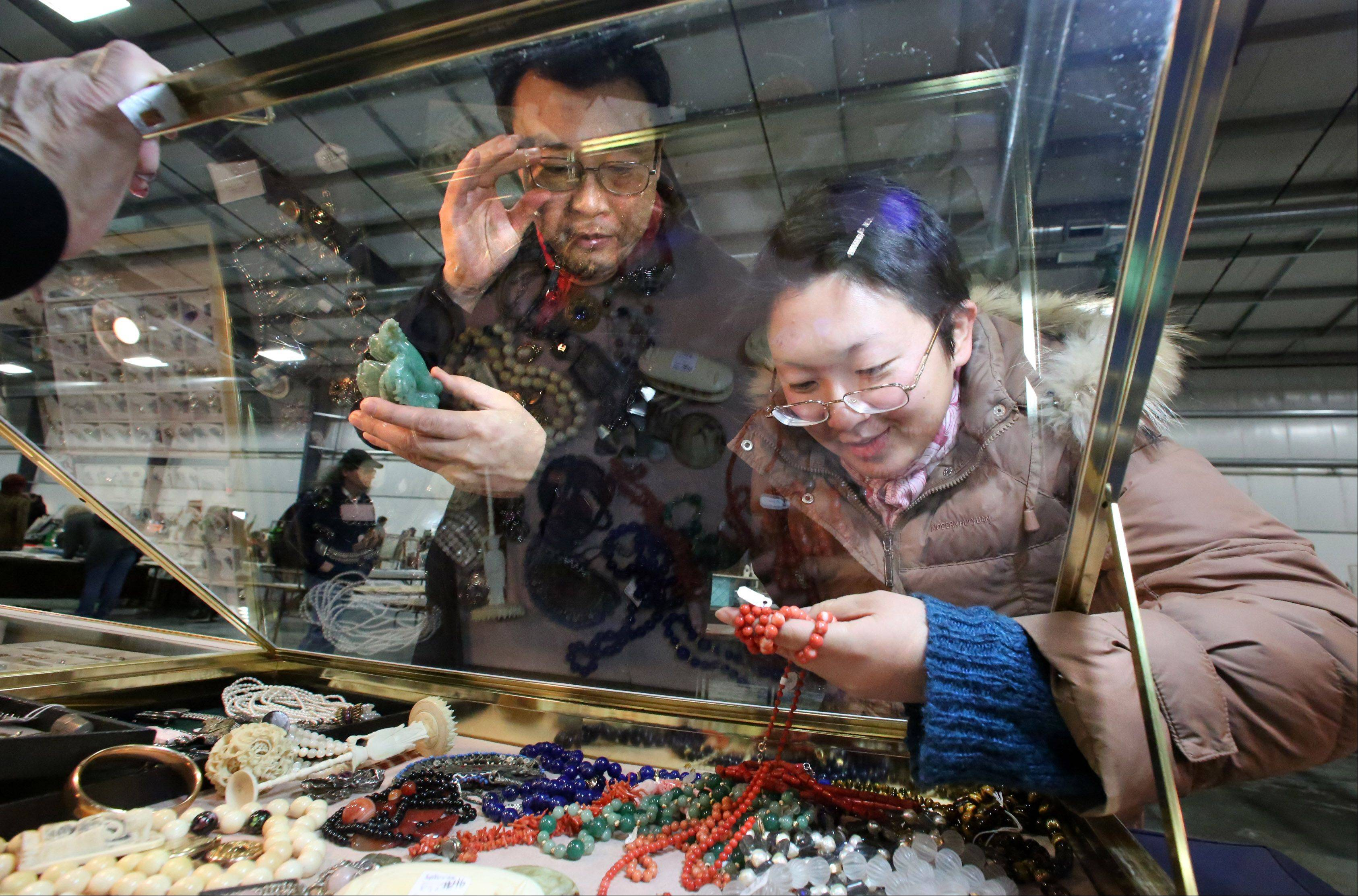 Bill and Natalie Wu of Chicago look at jade carvings and jewelry at the booth of Pam Benson of Orland Park at Zurko Antiques and Flea Market on Saturday at Lake County Fairgrounds in Grayslake.