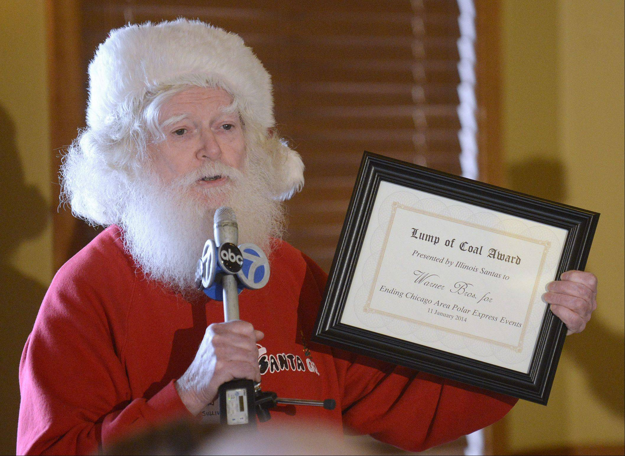 "John Sullivan of Streamwood holds up the ""Lump of Coal Award"" that will be mailed to Warner Bros. by the Santas and Mrs. Santas of Illinois. The group met in Aurora to say goodbye to ""Polar Express"" events like the one at Blackberry Farm."
