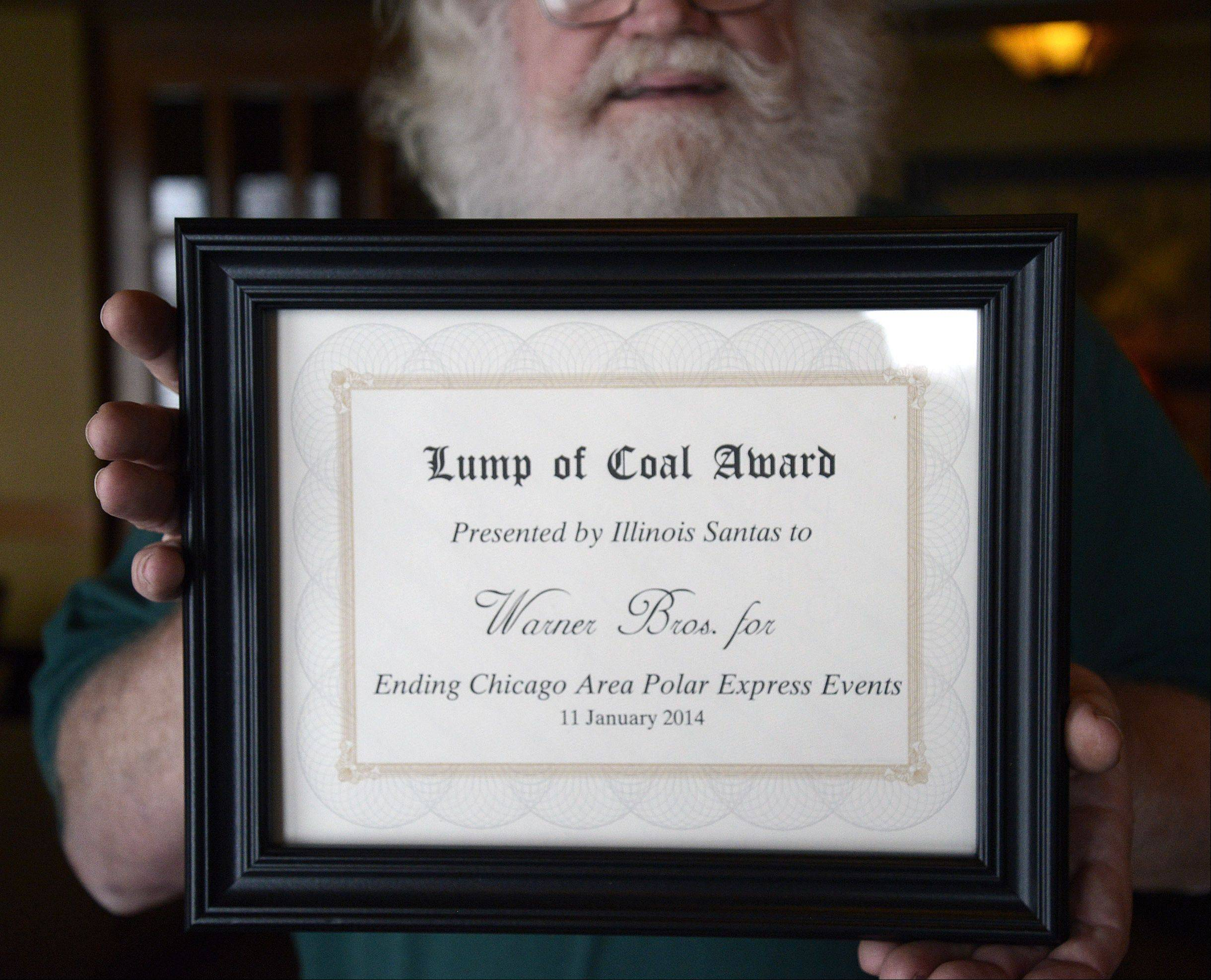 "Bill Wilson of Beloit, Wis., holds up the ""Lump of Coal Award"" that will be mailed to Warner Bros. by the Santas and Mrs. Santas of Illinois. The group met in Aurora to say goodbye to ""Polar Express"" events like the one at Blackberry Farm."
