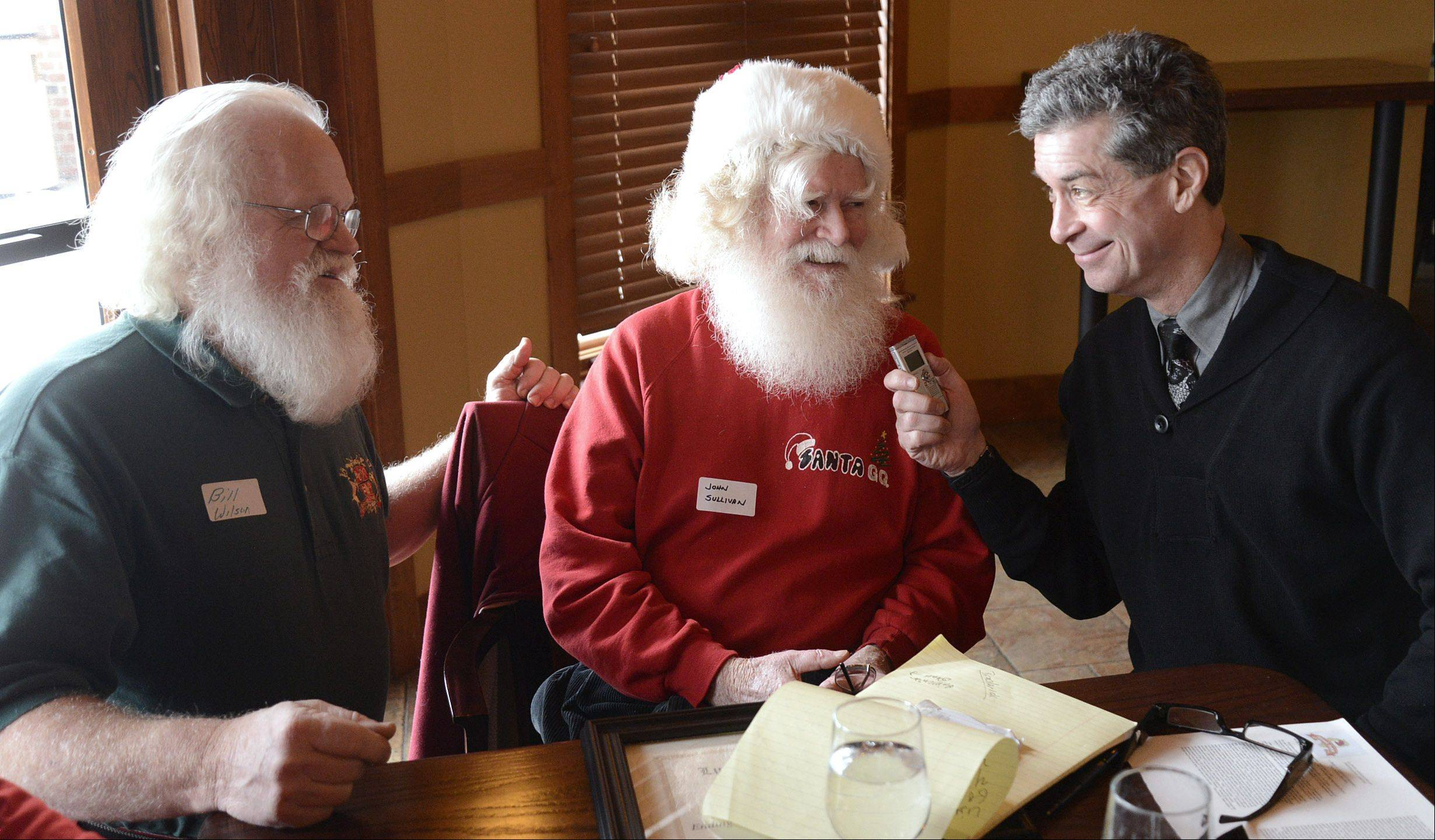 "Daily Herald reporter Dann Gire talks with Santas Bill Wilson of Beloit, Wis., left, and John Sullivan of Streamwood at the gathering of Santas and Mrs. Santas from around Illinois to say goodbye to ""Polar Express events."