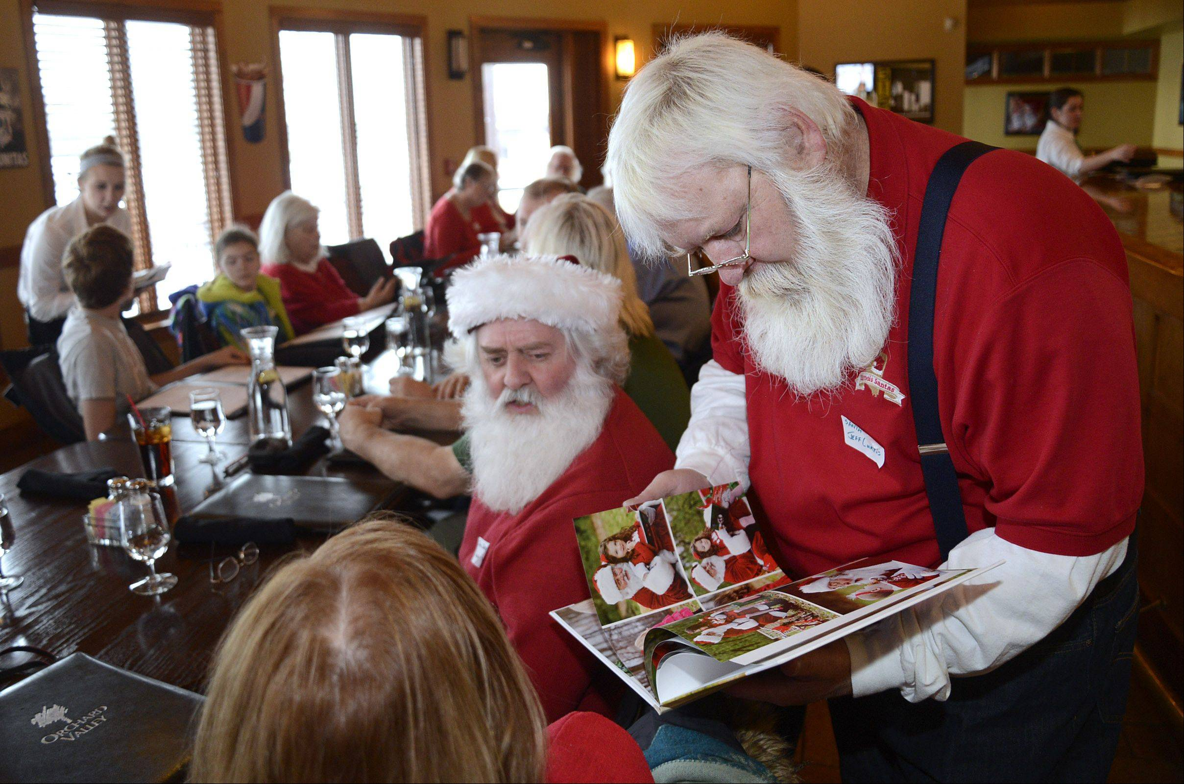 Jeff Curtis of Bartlett looks through the photo collage book of fellow Santa Sean Callaghan of Chicago, seated, during a gathering of Illinois Santas and Mrs. Santas Saturday in Aurora. Curtis has been a Santa for 15 years and Callaghan has been doing it three years.