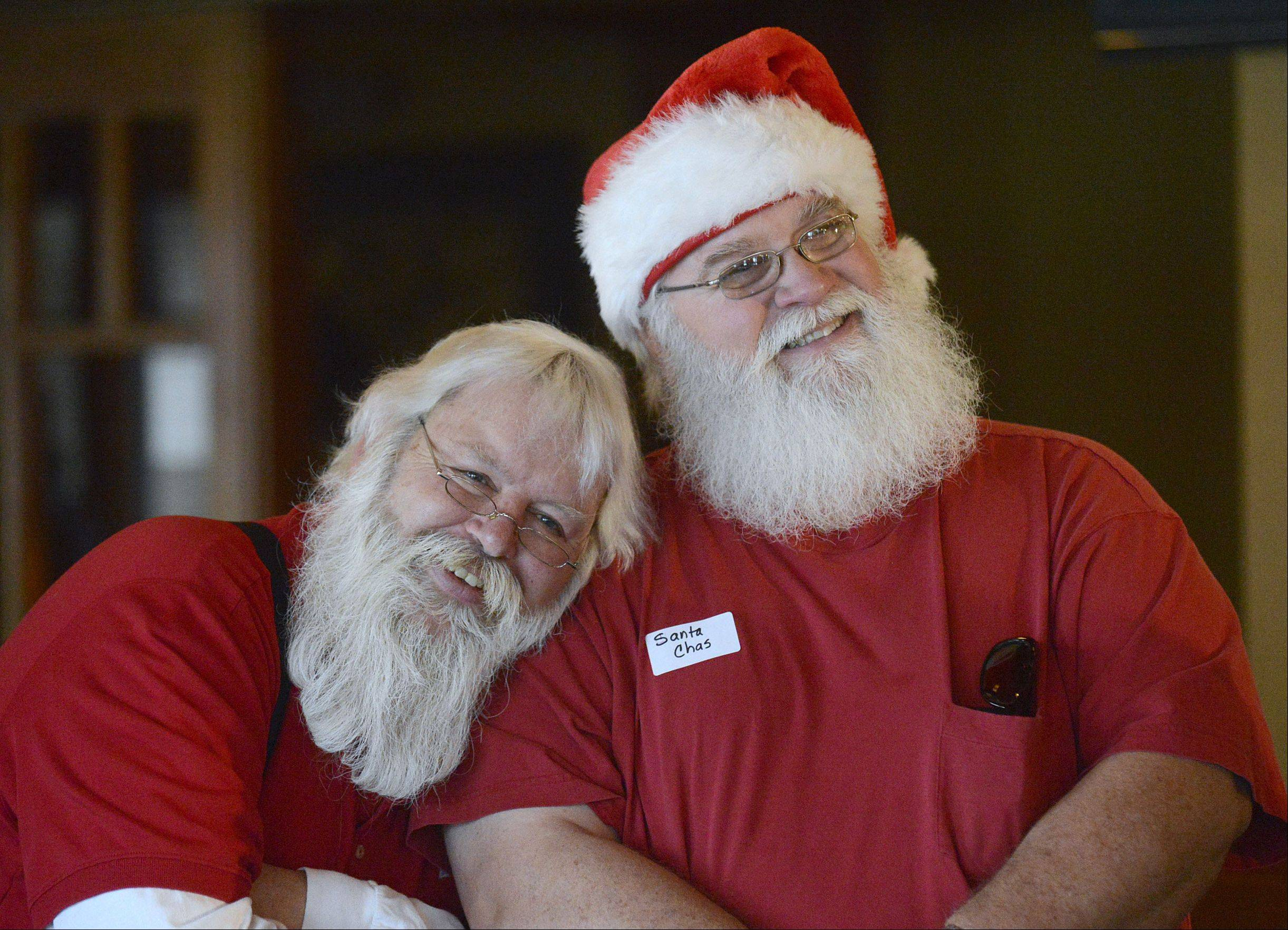 Jeff Curtis, left, of Bartlett and Charlie Miehle of Carol Stream pose for photos at a gathering of Santas and Mrs. Santas from around Illinois Saturday in Aurora.