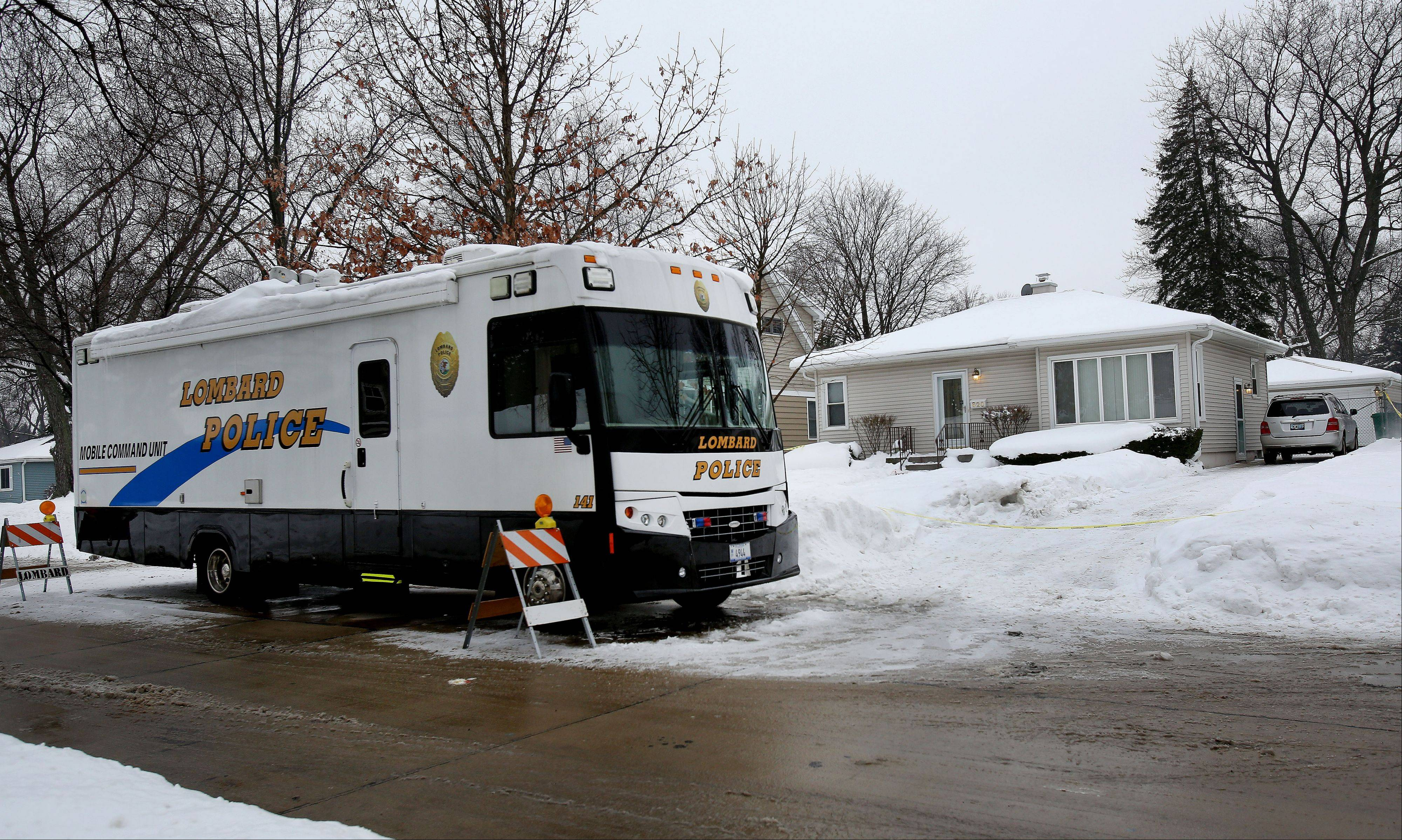 The Lombard Police mobile command unit sits Friday outside the Lombard house where Anka Miscevic, 48, is accused of attacking her husband, Zeljko Miscevic, 53, who later died.