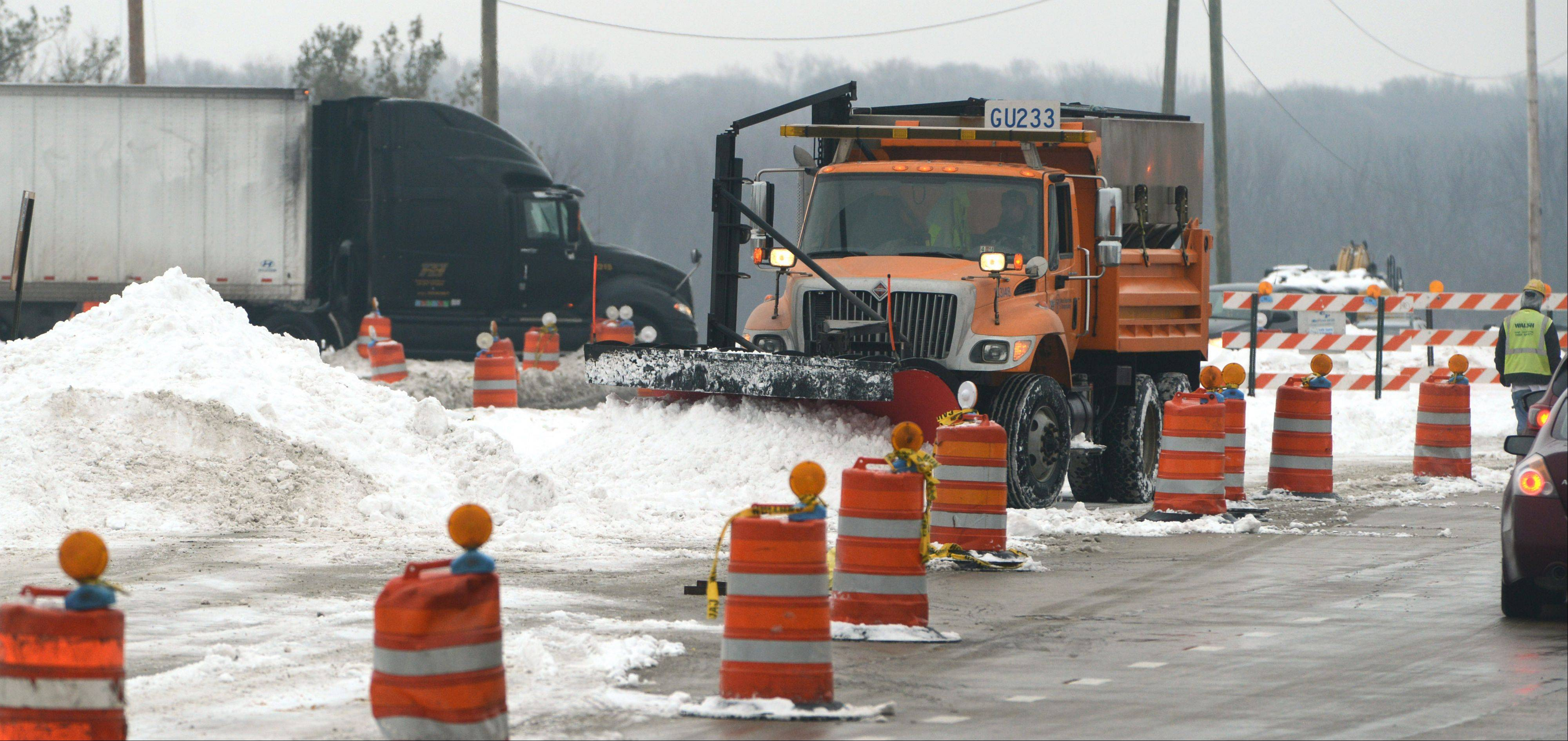 Road crews remove snow from the construction zone along Route 137, west of Route 21, in Libertyville Friday morning.
