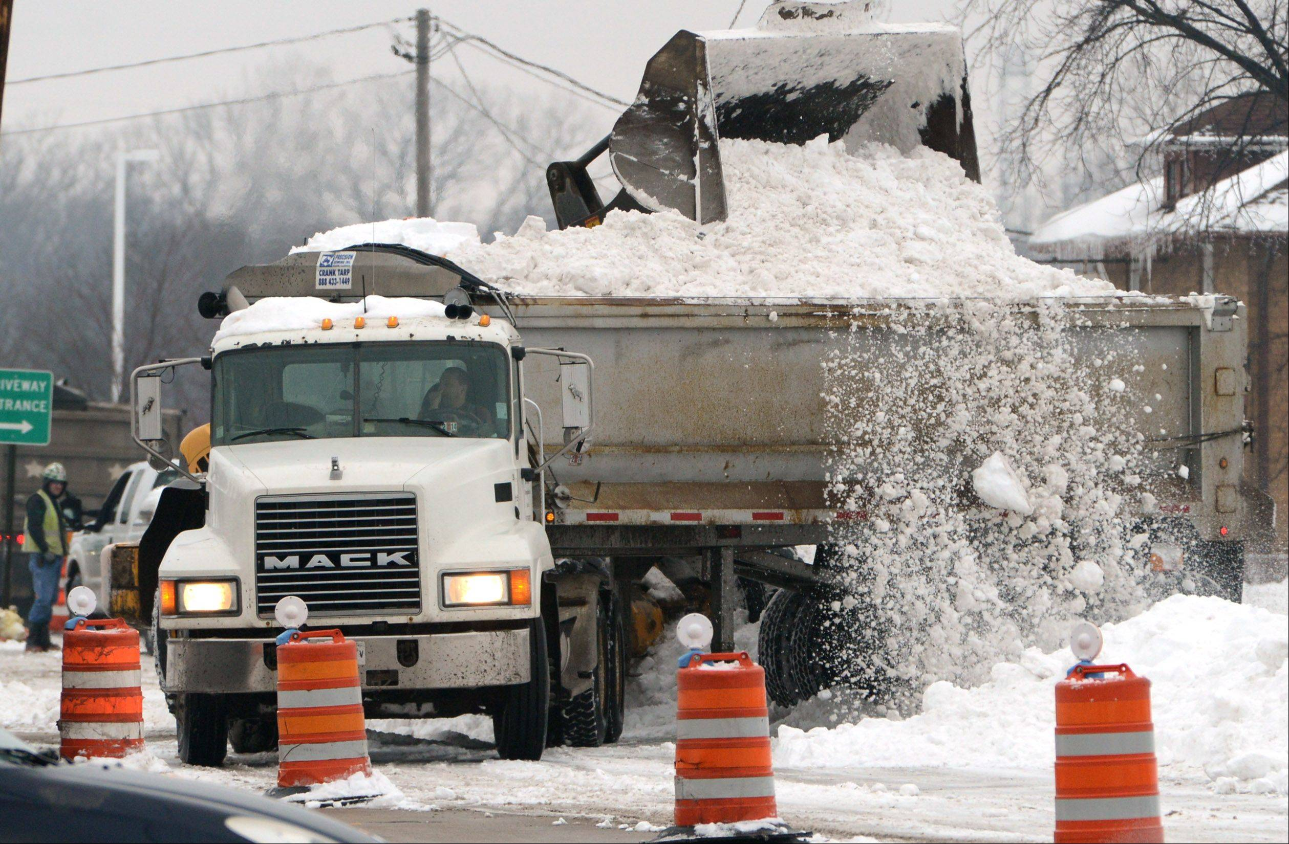 Snow is loaded for removal along Route 137 in Libertyville Friday morning. Road crews began clearing the snow so temporary pavement markings can be replaced and the new lanes opened.
