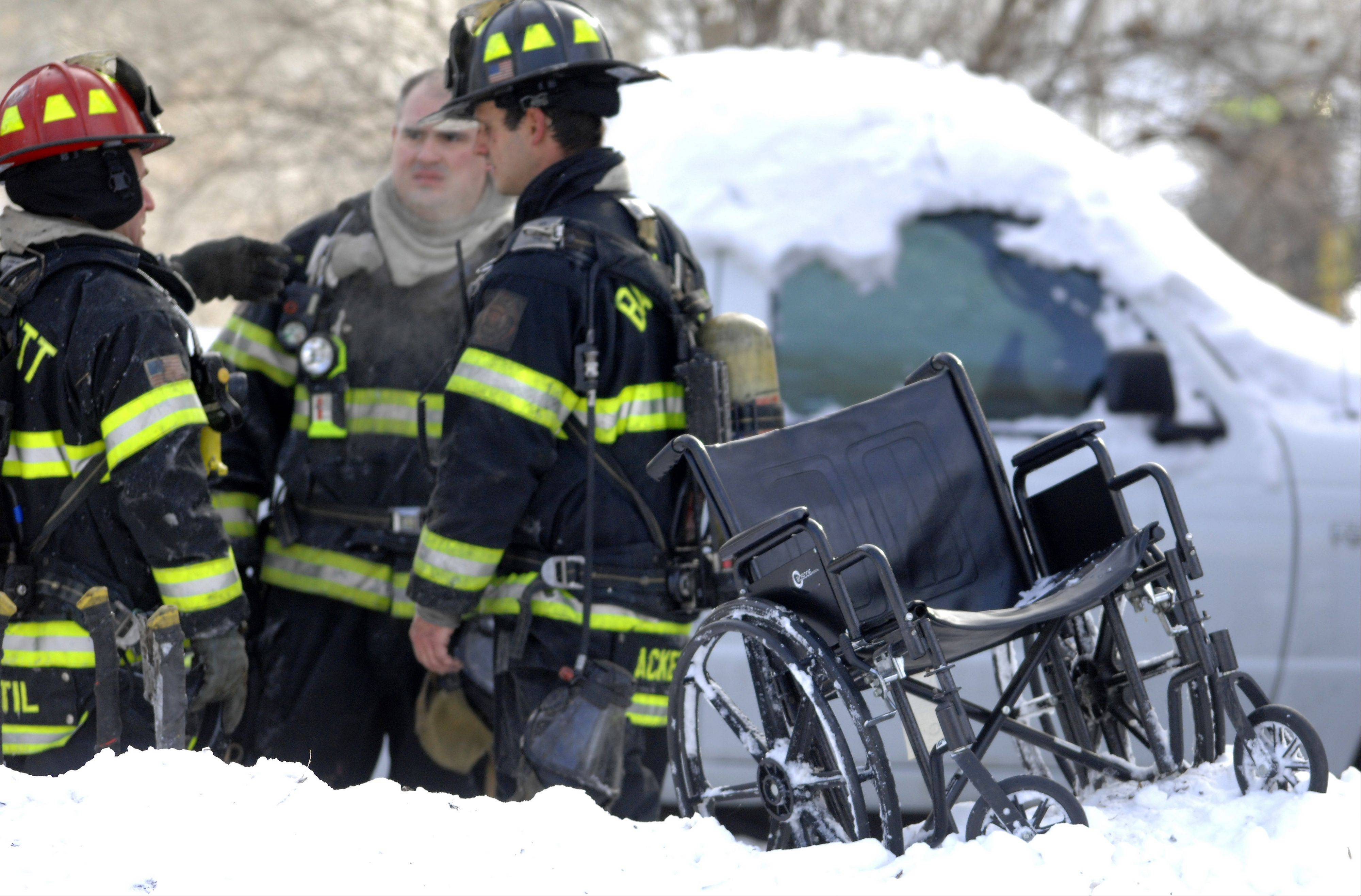 A wheelchair belonging to a woman who was rescued from a house fire Wednesday morning in South Elgin that killed her 72-year-old husband sits outside the fire scene.
