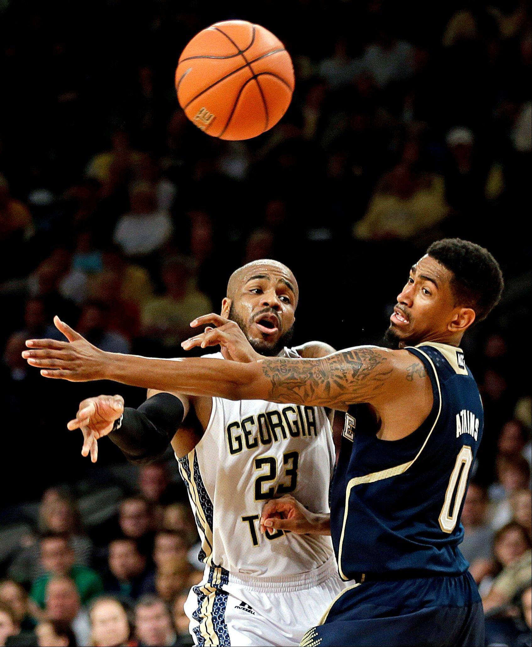 Georgia Tech's Trae Golden, left, passes the ball against the defense of Notre Dame's Eric Atkins in the second half of an NCAA college basketball game, Saturday, Jan. 11, 2014, in Atlanta. Georgia Tech won 74-69.