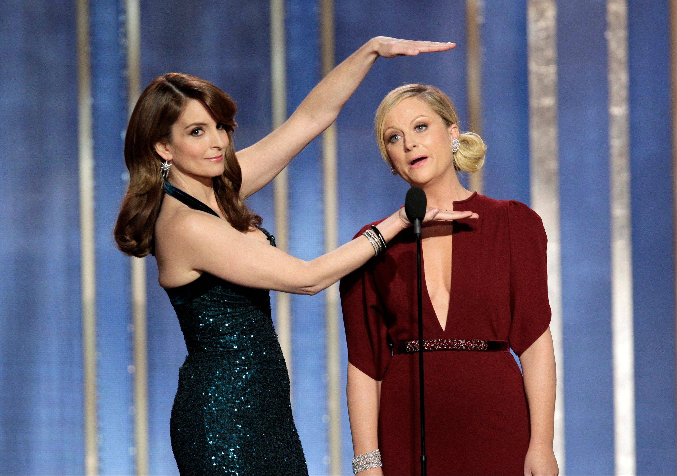 Tina Fey, left, and Amy Poehler return to host the Golden Globe Awards.