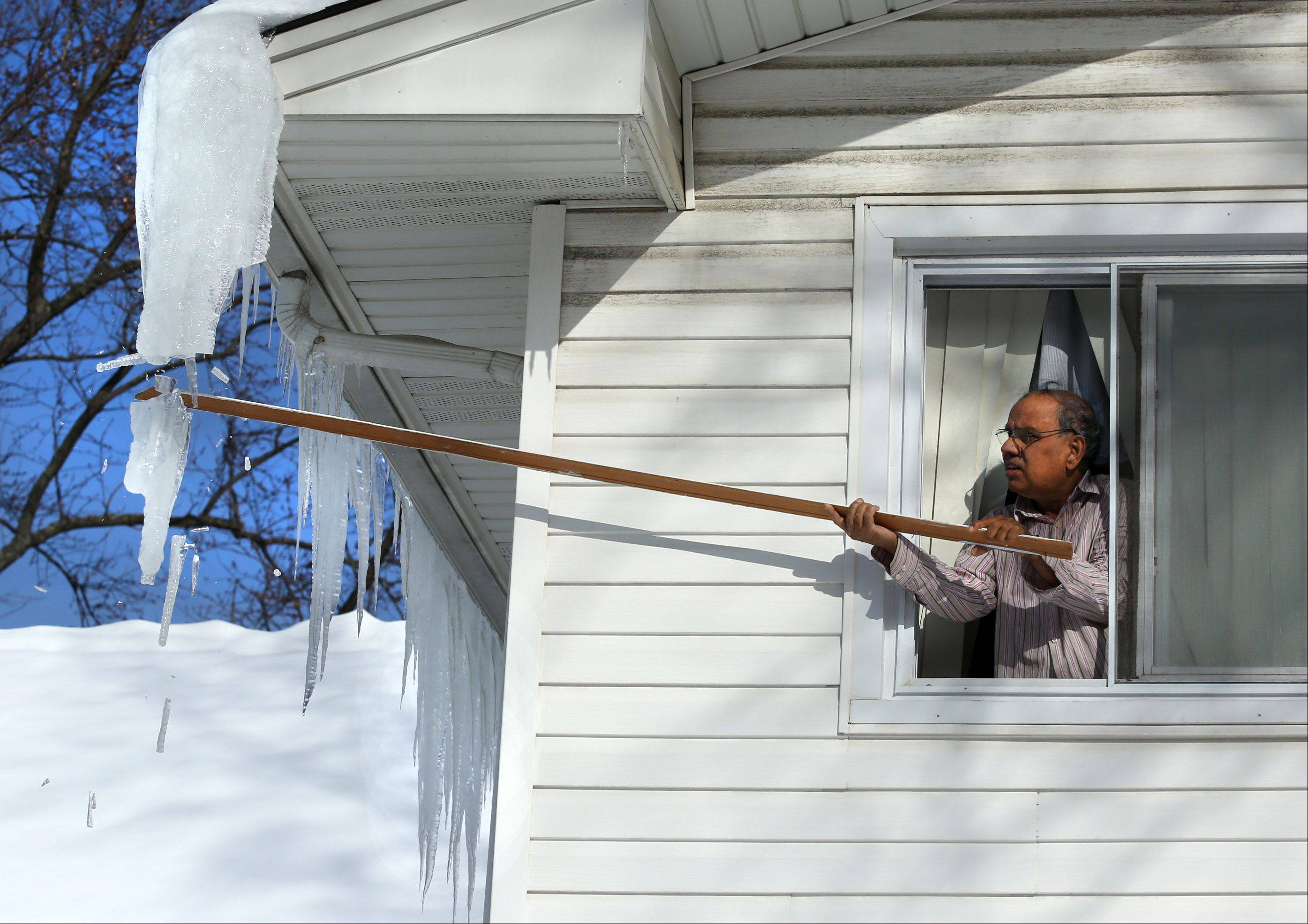 George LeClaire/gleclaire@dailyherald.com Leaning out a second floor window, Mohammad Mohyuddin uses a stick to knock icicles off of his home�s roof in Rolling Meadows on Wednesday.