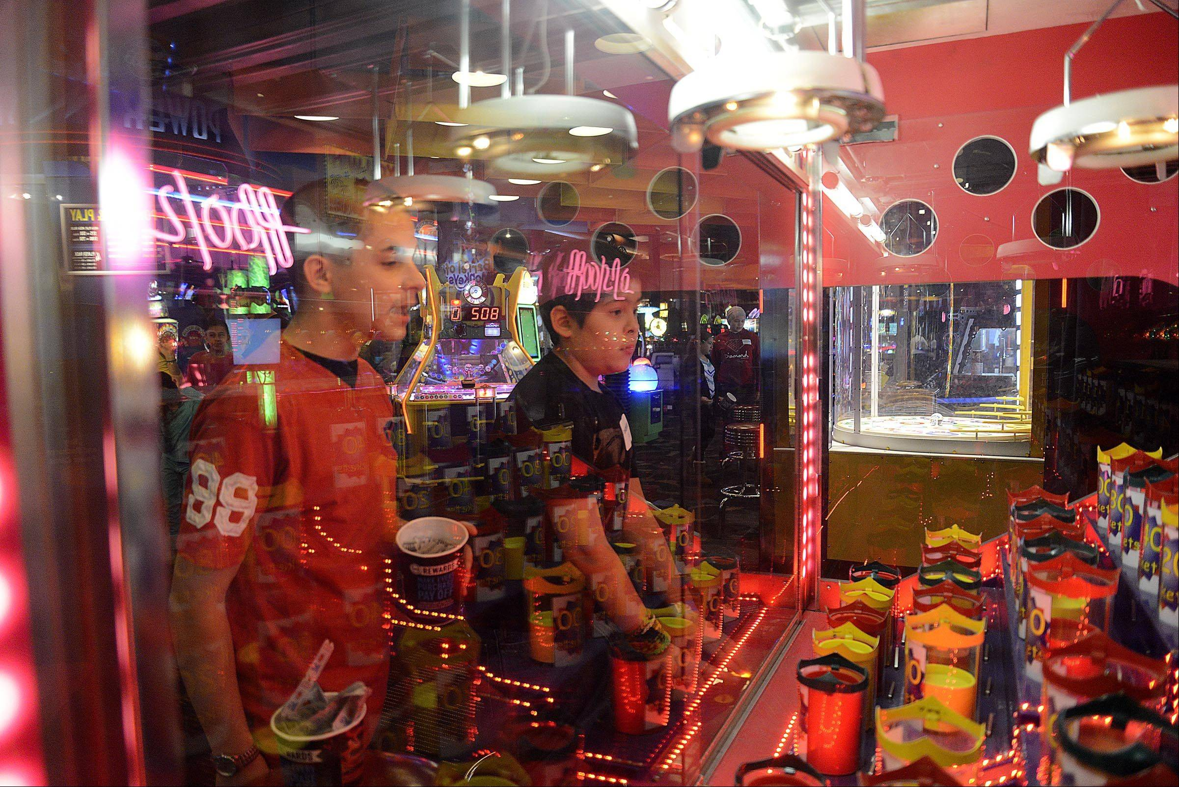 Zachary Aceves, 10, right, of Chicago, plays a game as his older brother Alex, 16, coaches him Sunday at Dave and Buster�s in Addison. They were there for the Leukemia Research Foundation Kids Party. Zachary is a six-year leukemia survivor.