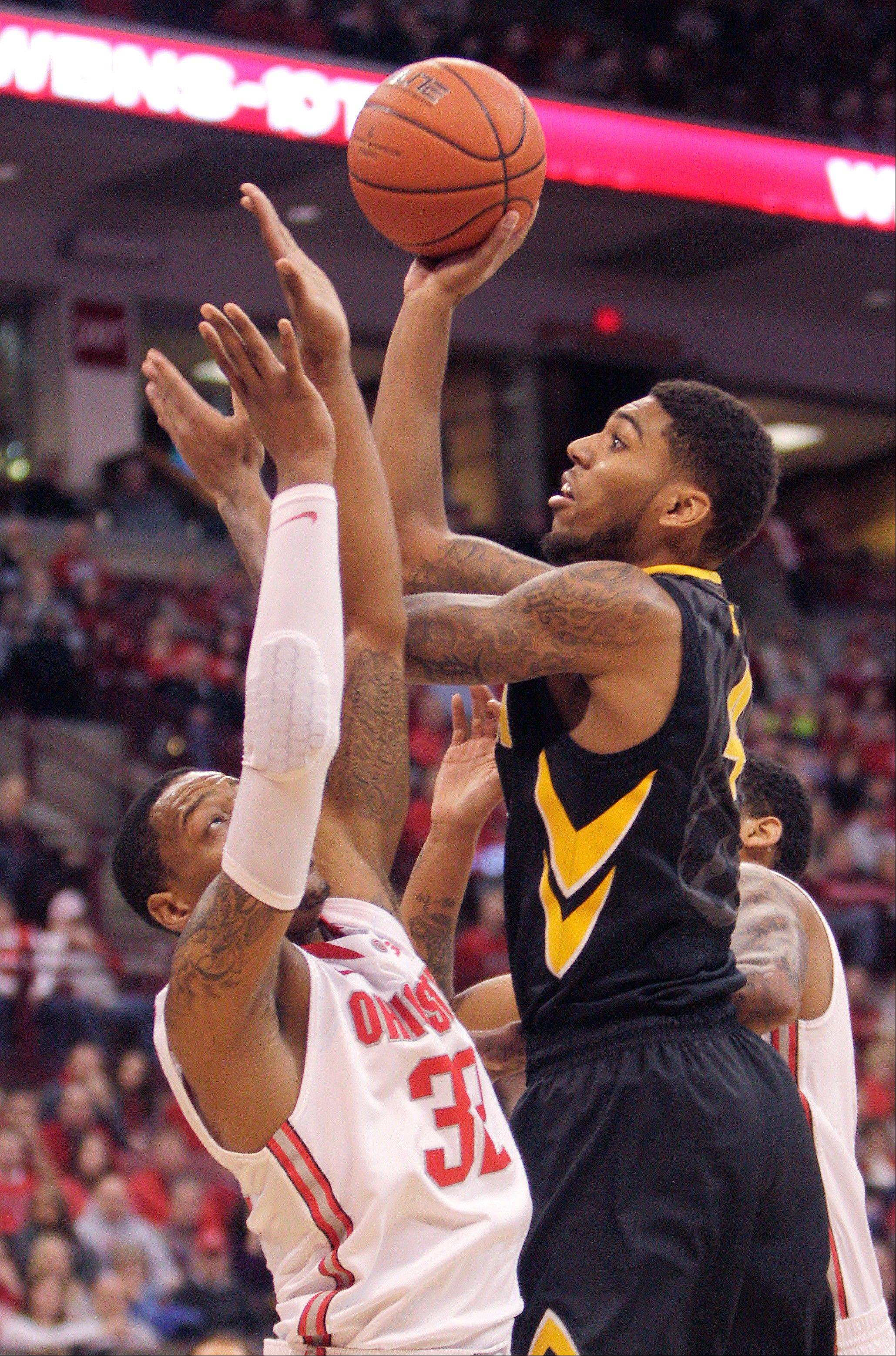 Iowa�s Roy Devyn Marble, right, shoots over Ohio State�s Lenzelle Smith during the first half of Sunday�s game in Columbus, Ohio.