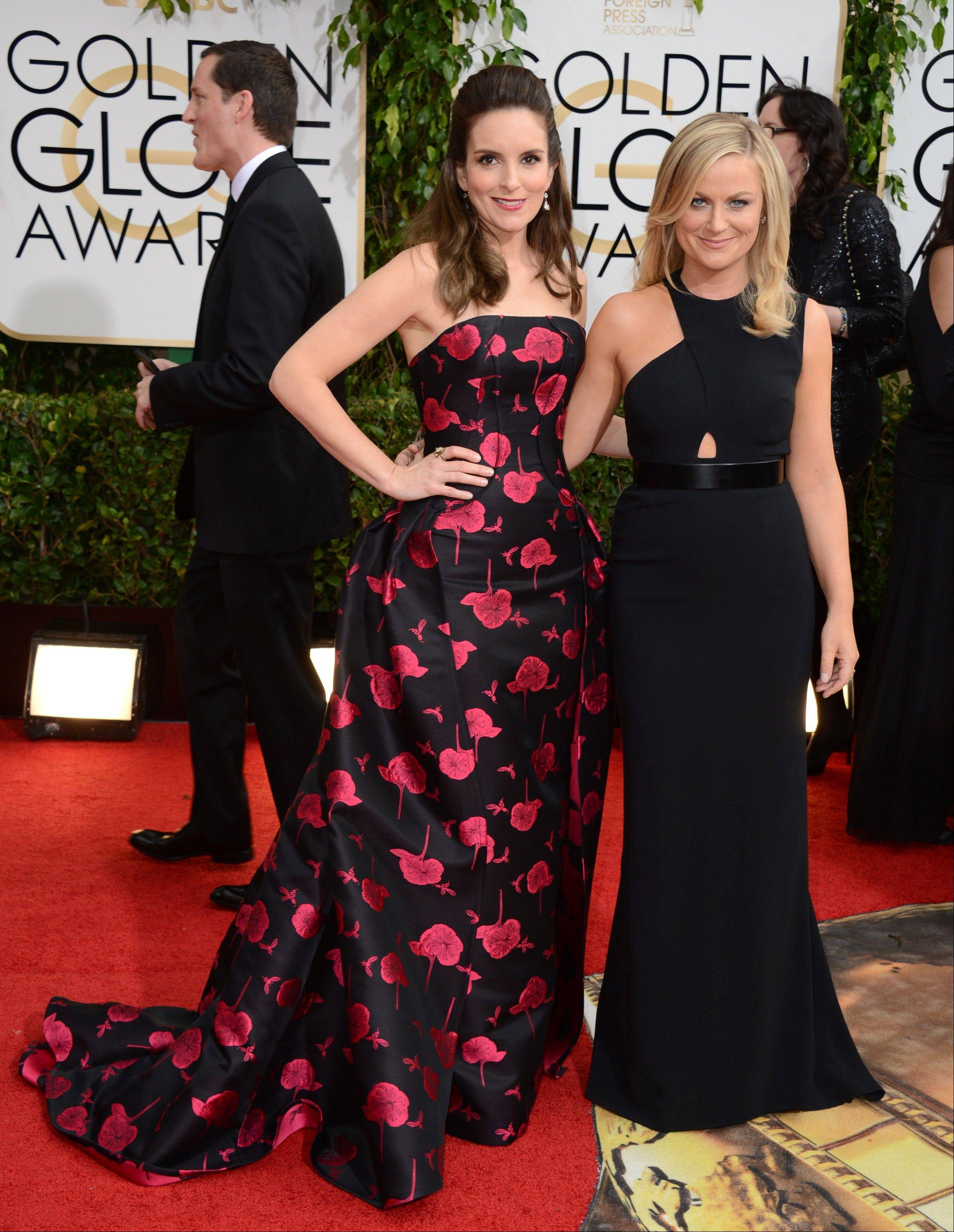 Golden Globes hosts Tina Fey, left, and Amy Poehler walk the red carpet Sunday in Beverly Hills, Calif.