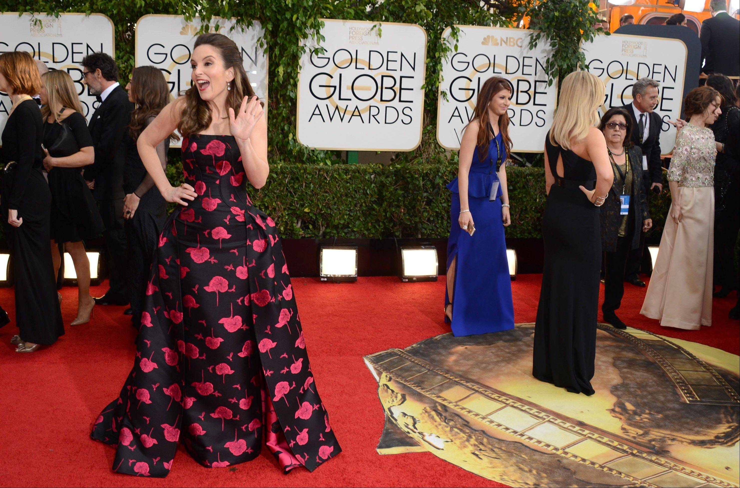 Golden Globes host Tina Fey waves to the crowd while she waits for her co-host and real life best friend Amy Poehler to finish with the press line.