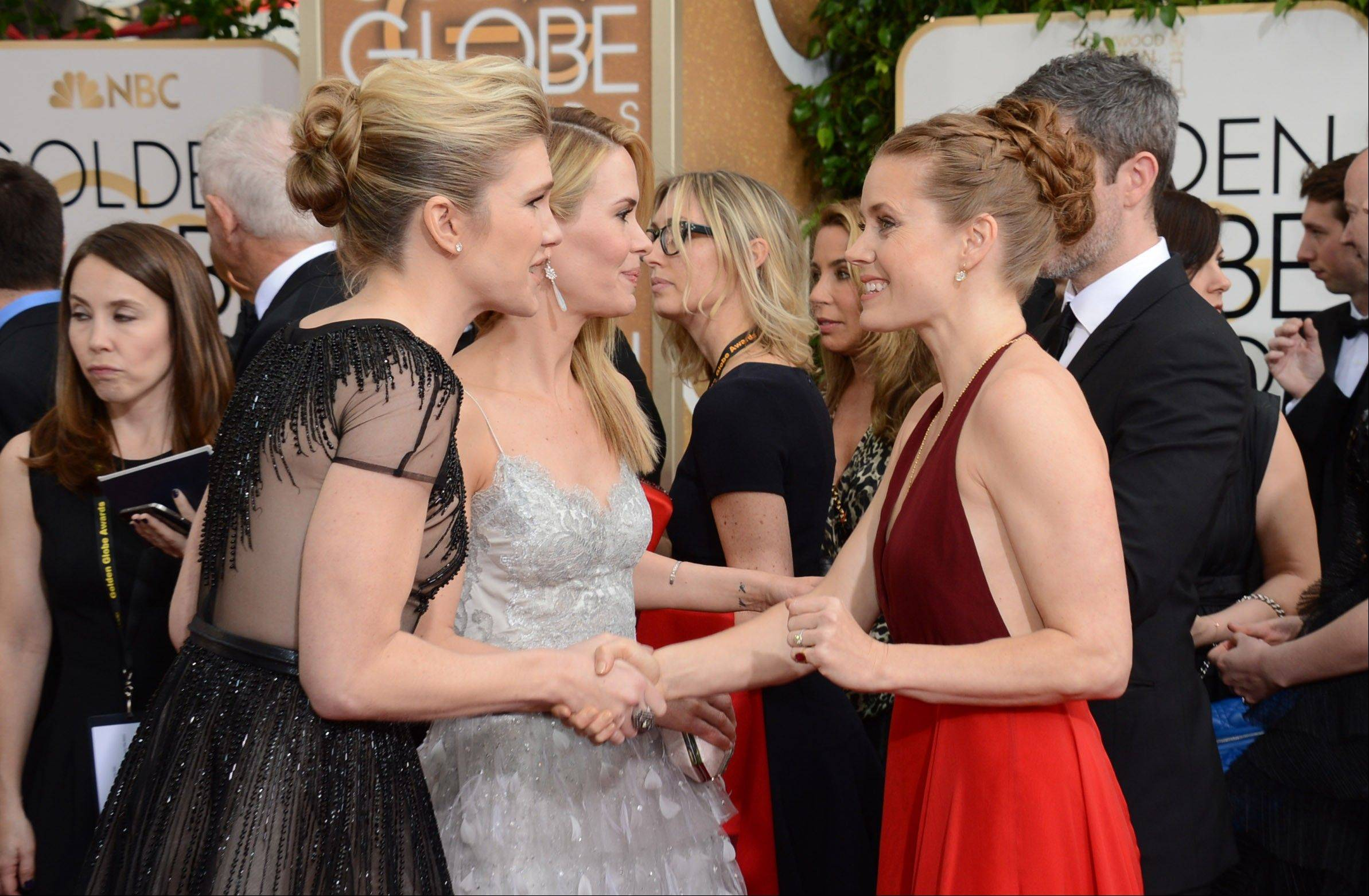 Actresses, from left, Lily Rabe, Sarah Paulson, and Amy Adams arrive at the 71st annual Golden Globe Awards.