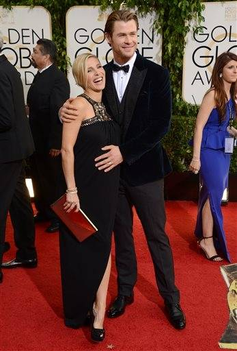 """Thor"" star Chris Hemsworth gives wife Elsa Pataky's baby bump a little rub as the couple walk the red carpet."