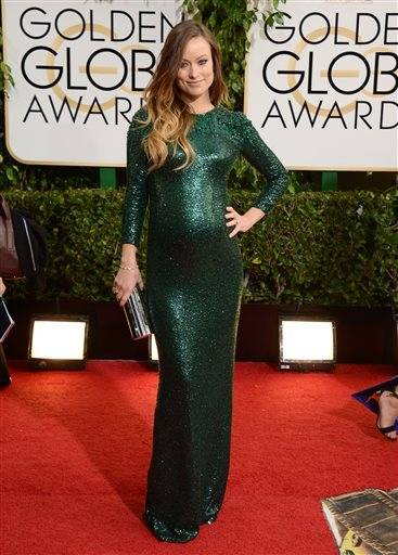 A pregnant Olivia Wilde poses on the red carpet looking every inch a star in this emerald gown.