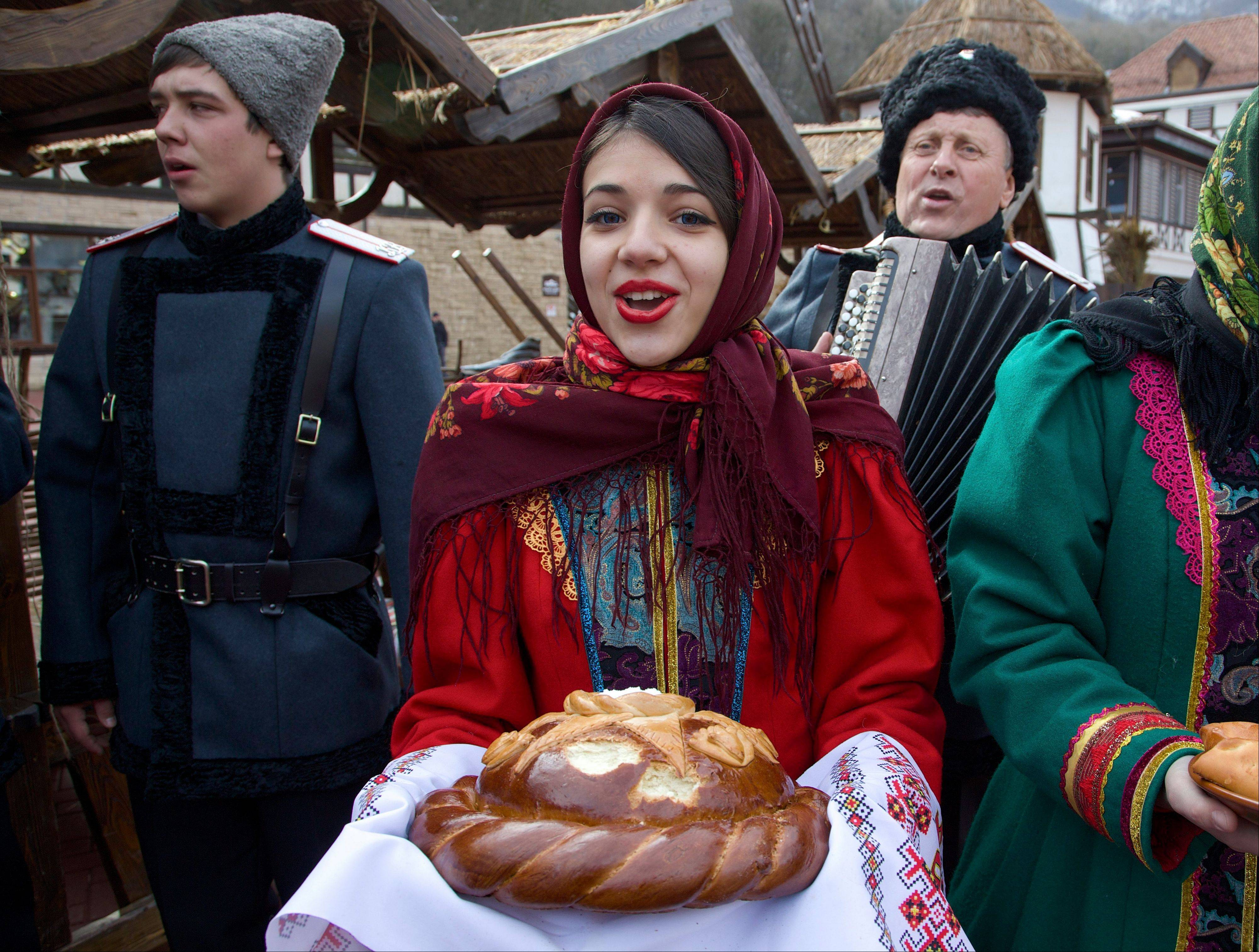Artists dressed in folk costumes sing as they welcome guests at a street in Rosa Khutor, east of Sochi, Russia. Sochi has long been a choice destination for Russia's political elite. Joseph Stalin's summer residence in Zeleni Mys even features a wax mannequin of the dictator at his desk.