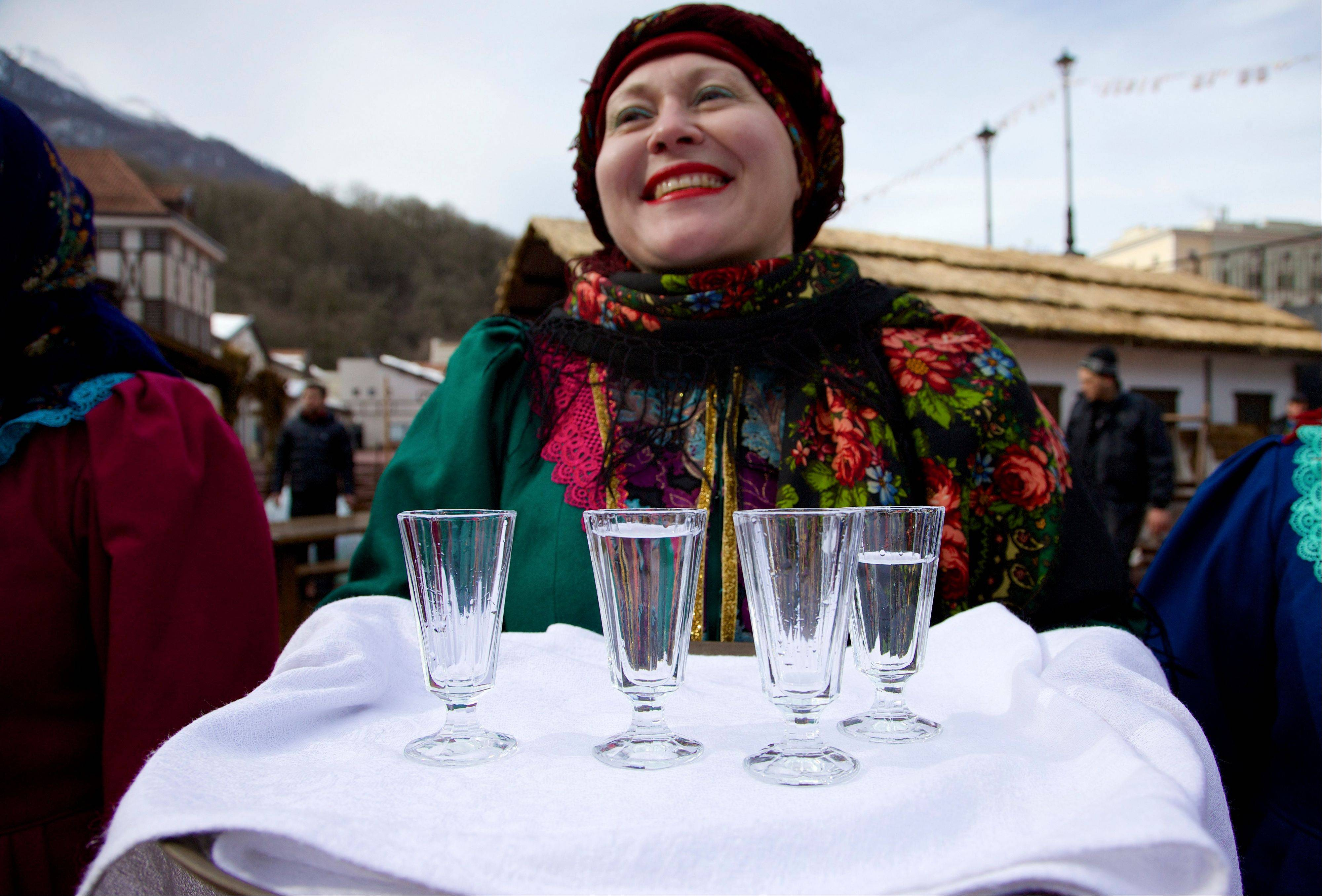 A woman in a traditional folk costume welcomes guests with a beverage at a street in Rosa Khutor, east of Sochi, Russia.