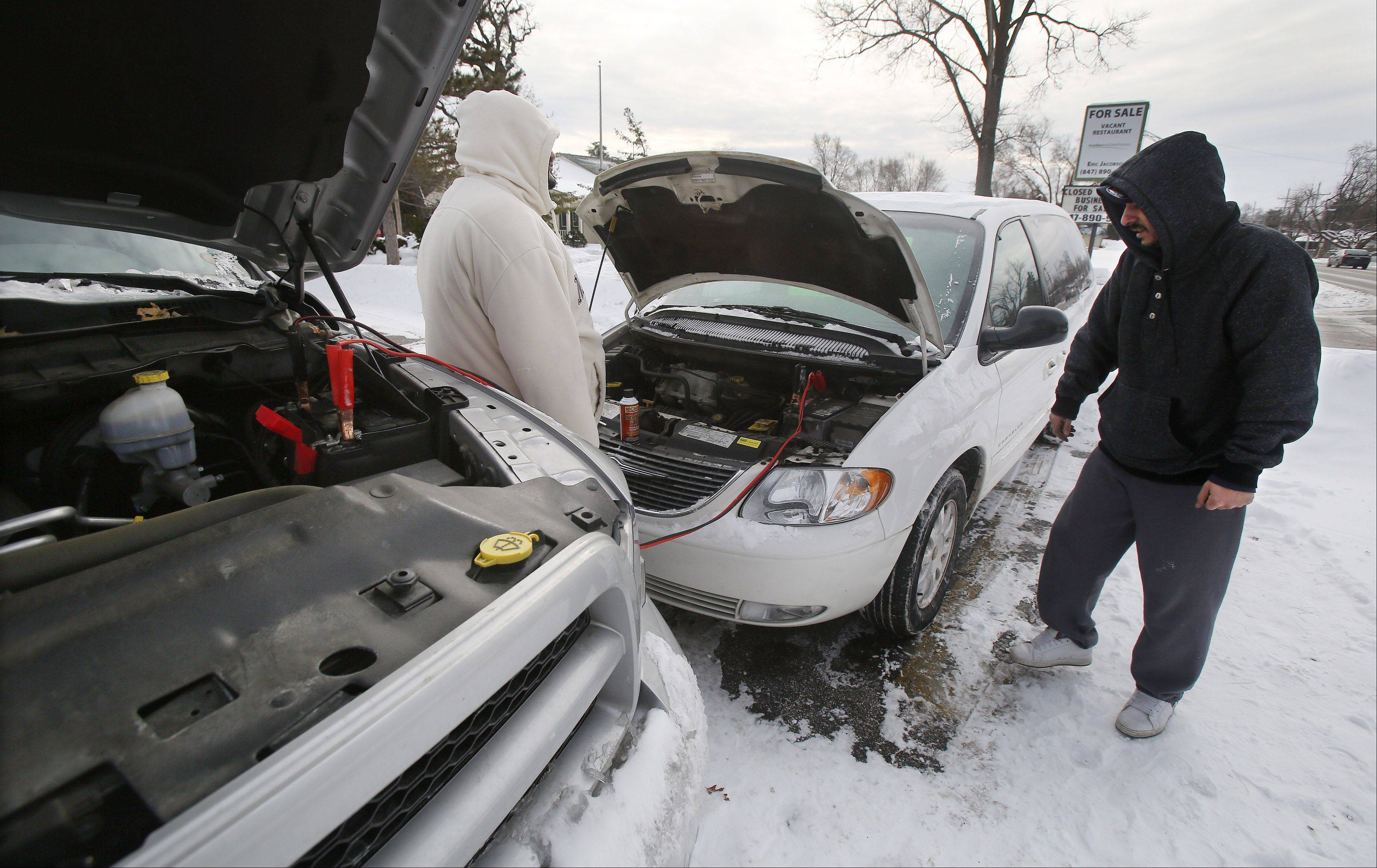 Gilbert R. Boucher II/gboucher@dailyherald.comBrothers Jimmy and Angelo Prier, right, try to jump start their car in Grayslake during the brutal cold on Tuesday.