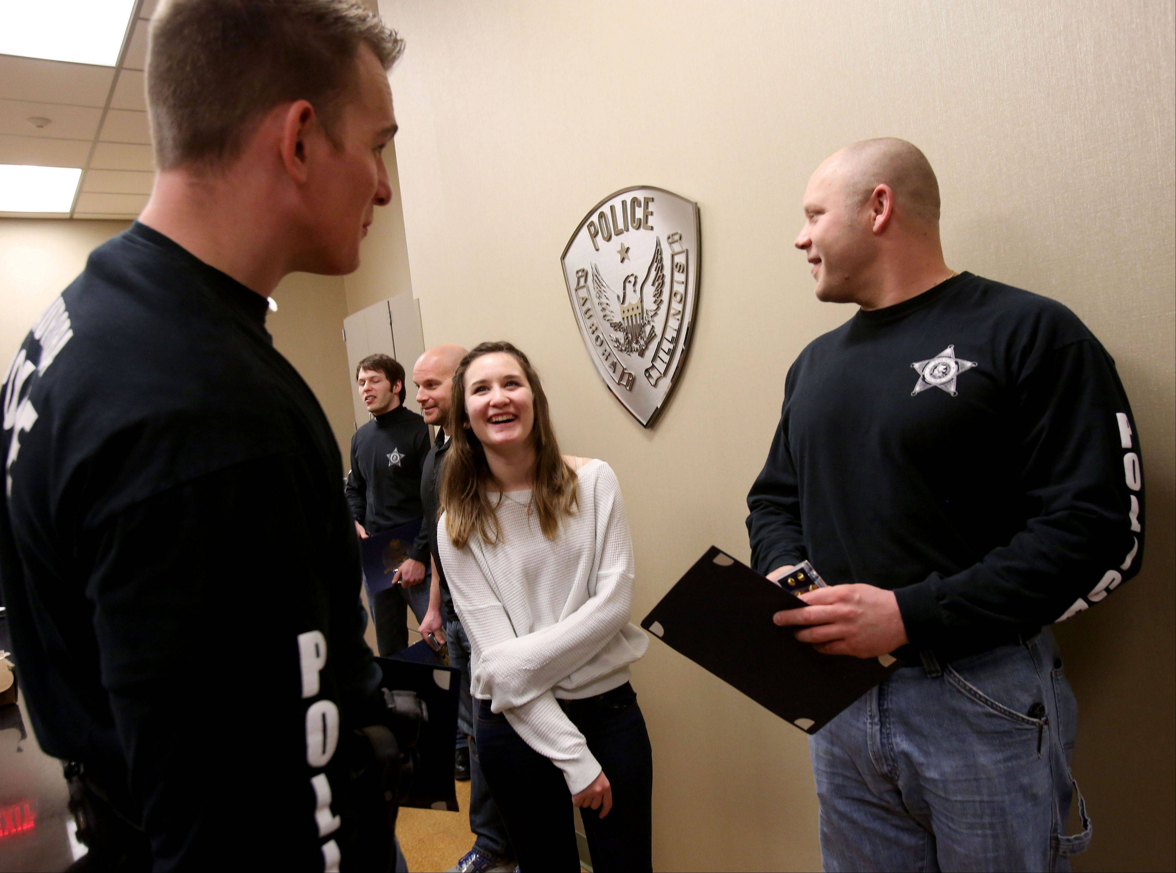 Bev Horne/bhorne@dailyherald.comAnnie Prosser, 15, chats with officers Edwin Doepel, left, and W. Joshua Sullivan after the local Fox Valley Chapter of the Sons of the American Revolution recognized seven Aurora police officers who saved her life from drowning last year when a car she was in went into a retention pond.