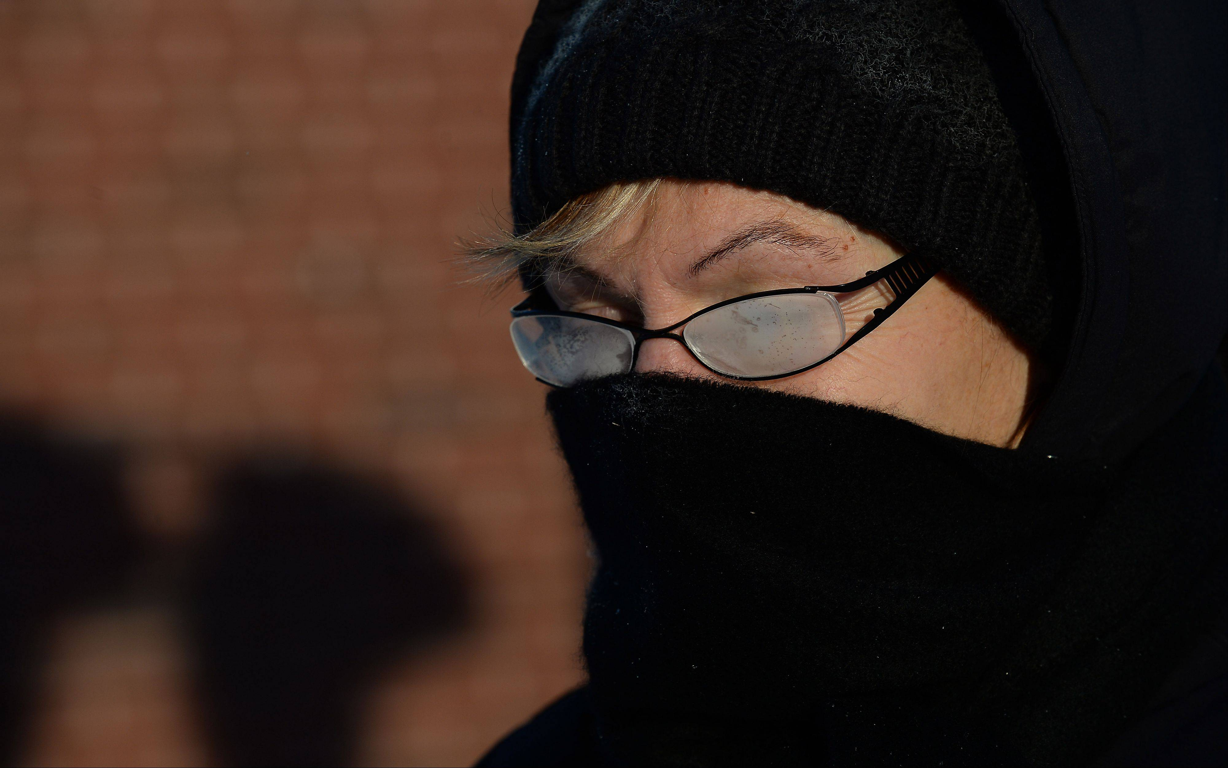 Mark Welsh/mwelsh@dailyherald.comKaren Morgan, of Arlington Heights, braves the cold with fogged glasses and scarf at the Arlington Heights train station.