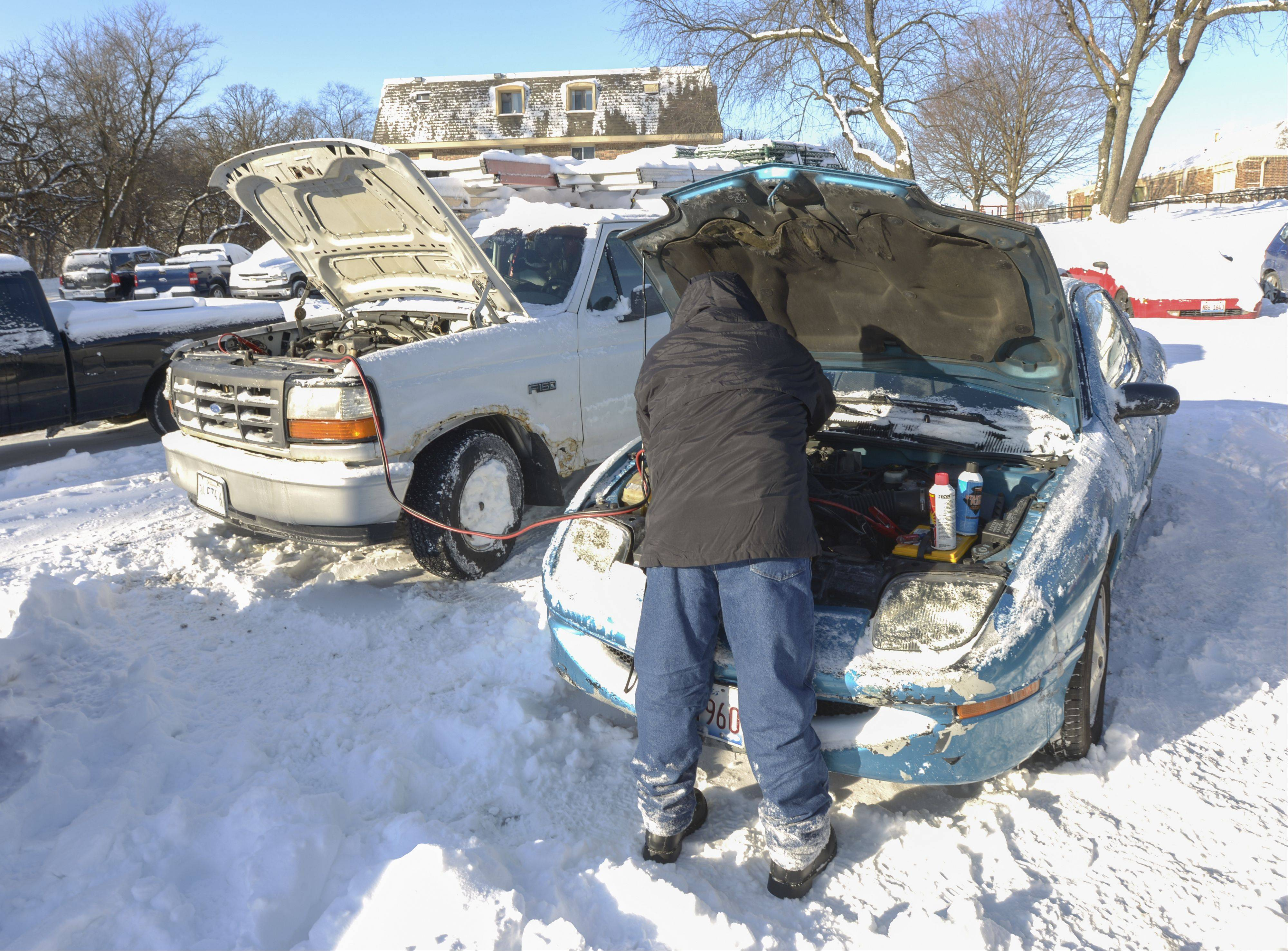 Mark Black/mblack@dailyherald.comRoberto Tiro works on getting his car started by trying to jump it with a work truck, at the Aspen Ridge Apartments in West Chicago. Tiro was having difficulty getting the car started even using some starter fluid and jumper cables.