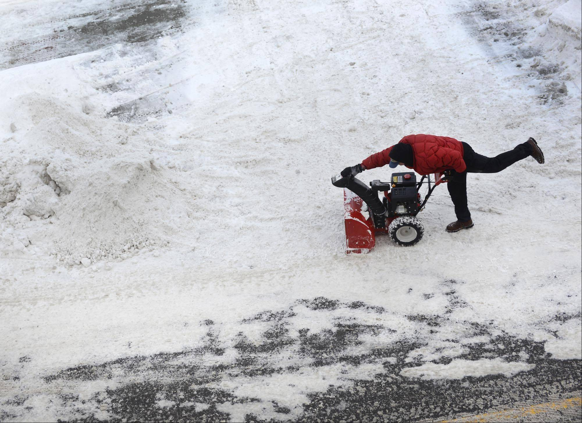 John Starks/jstarks@dailyherald.comJohn Hedlund, of Elgin, adjusts the chute of his snowblower while he clears the parking lot of the Art Space Lofts on Fulton Street in downtown Elgin Tuesday. Temperatures were warmer than Monday's -42 windchill, but he said he didn't notice.