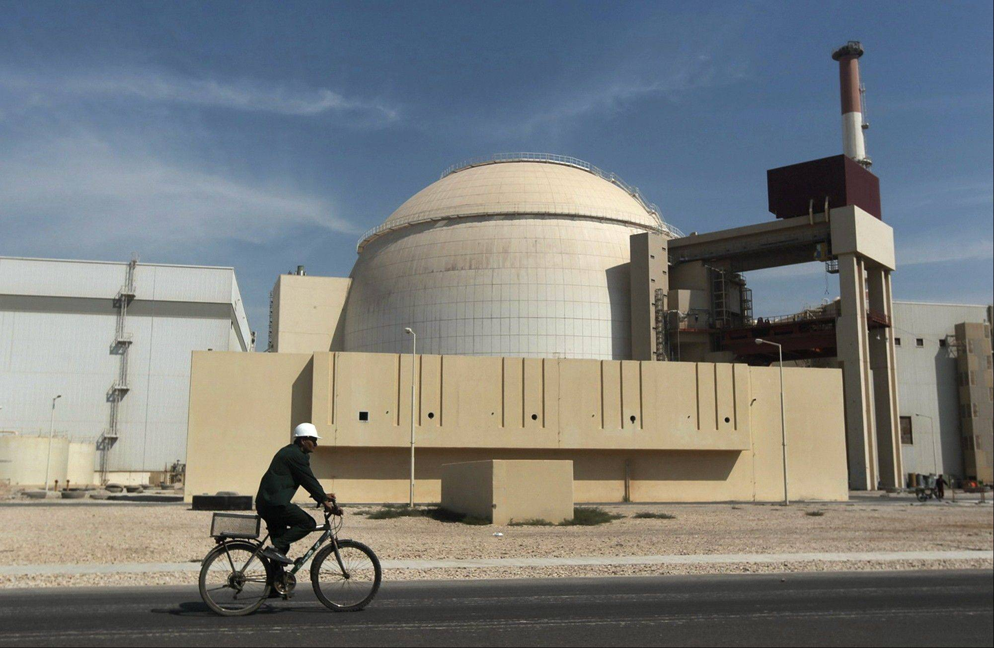 A worker rides a bicycle in front of the reactor building of the Bushehr nuclear power plant, just outside the southern city of Bushehr.