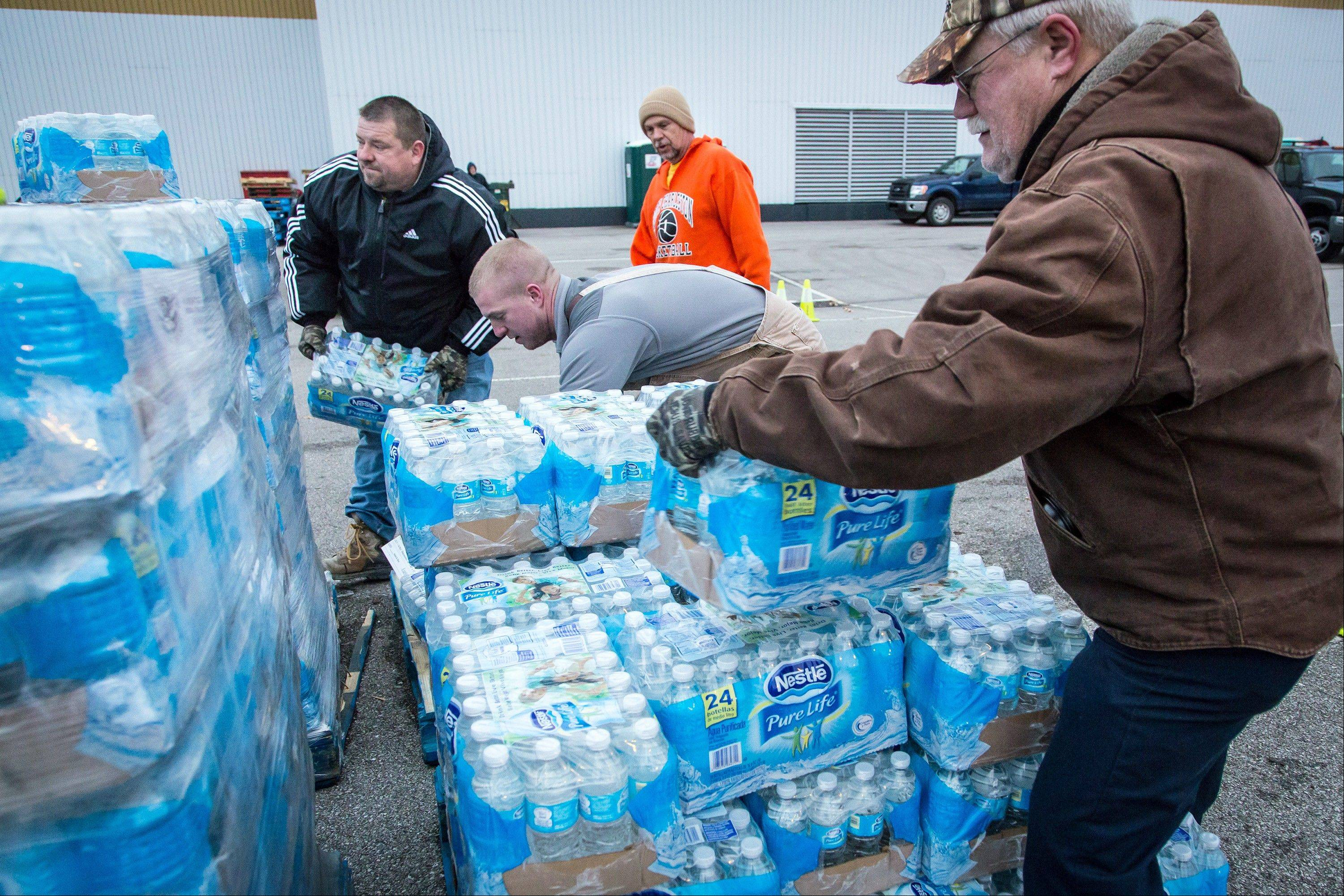 Public works employees assist local residents in South Charleston, W.V., in obtaining bottled water on Sunday morning. A chemical spill Thursday in the Elk River has contaminated the public water supply in nine counties.