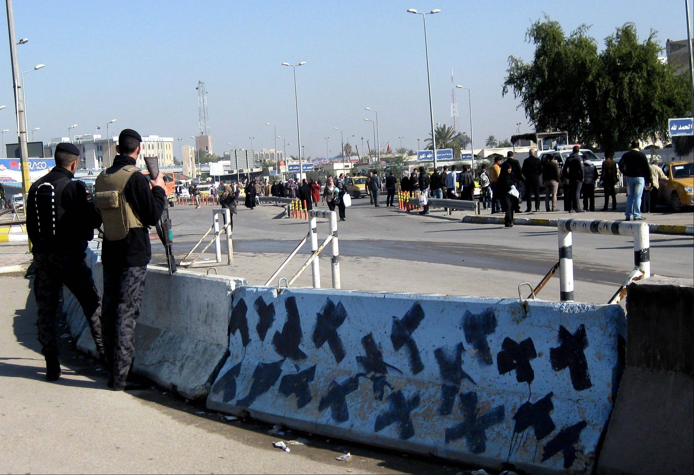 Iraqi security forces stand guard Sunday at the site of a bomb attack in Baghdad.