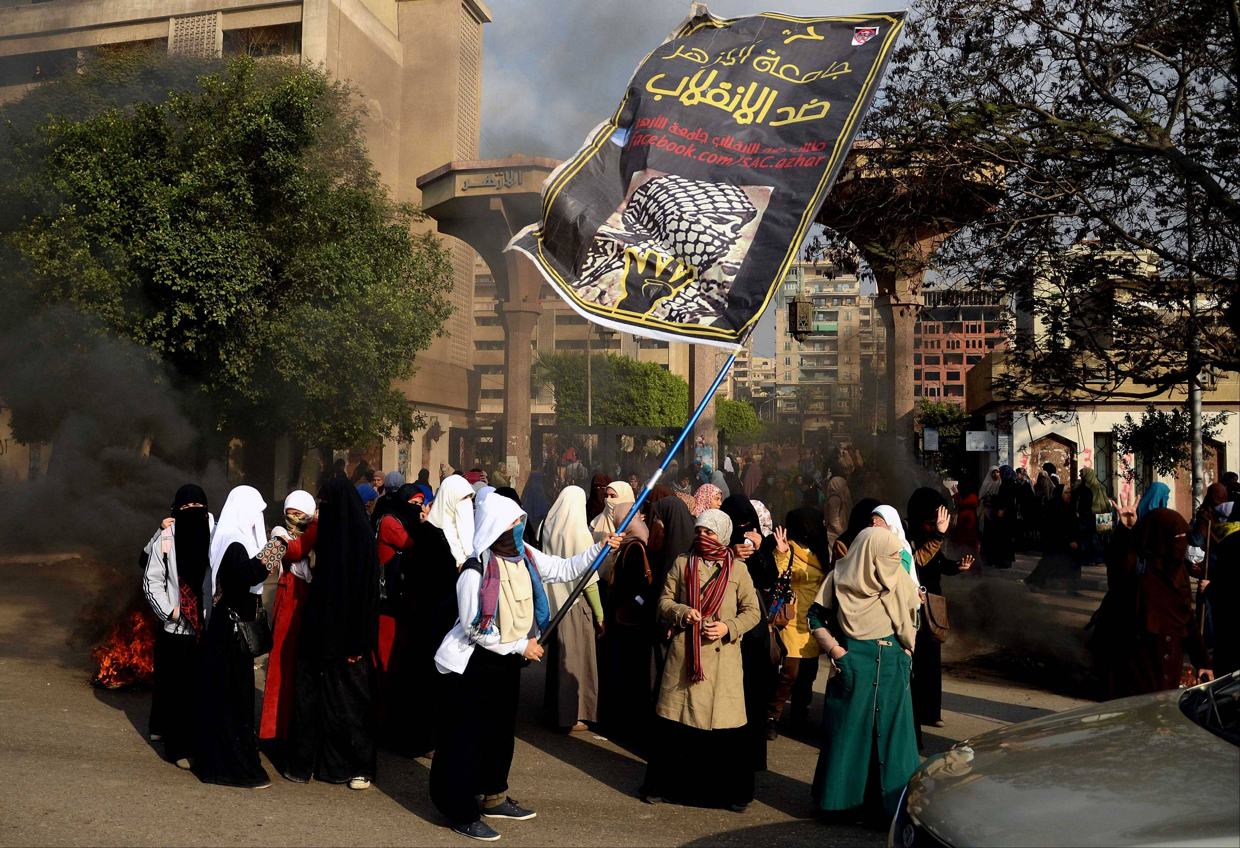 "A supporter of Egypt's ousted President Mohammed Morsi and Al-Azhar University female student holds a banner with Arabic that reads, ""Al-Azhar University is against the coup,"" during clashes with security forces in front of the university in Cairo Sunday."