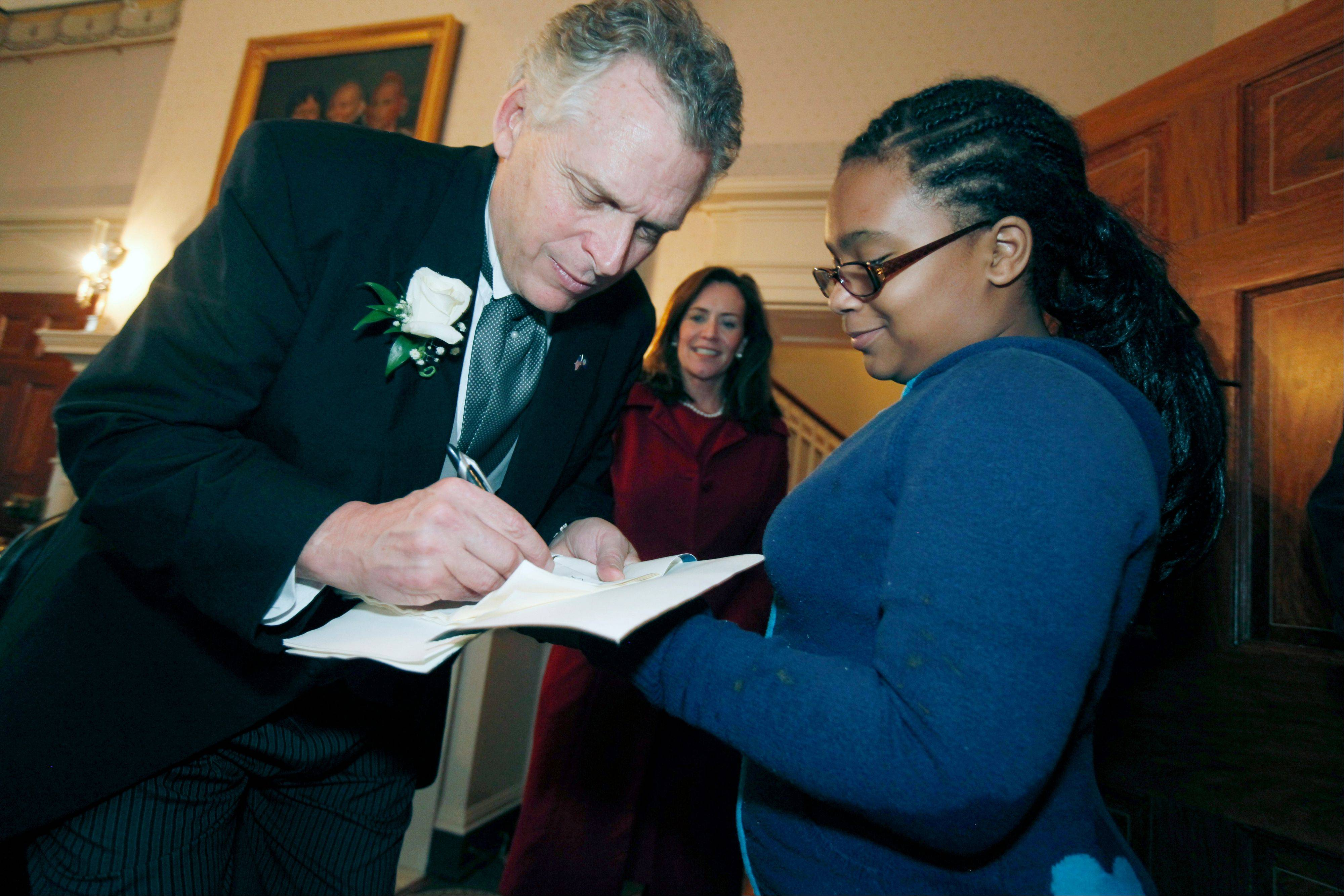 Governor Terry McAuliffe signs an autograph Saturday for Daisa Bridges, 12, as McAuliffe's wife Dorothy, center, looks on during an open house at the Executive Mansion in Richmond, Va.