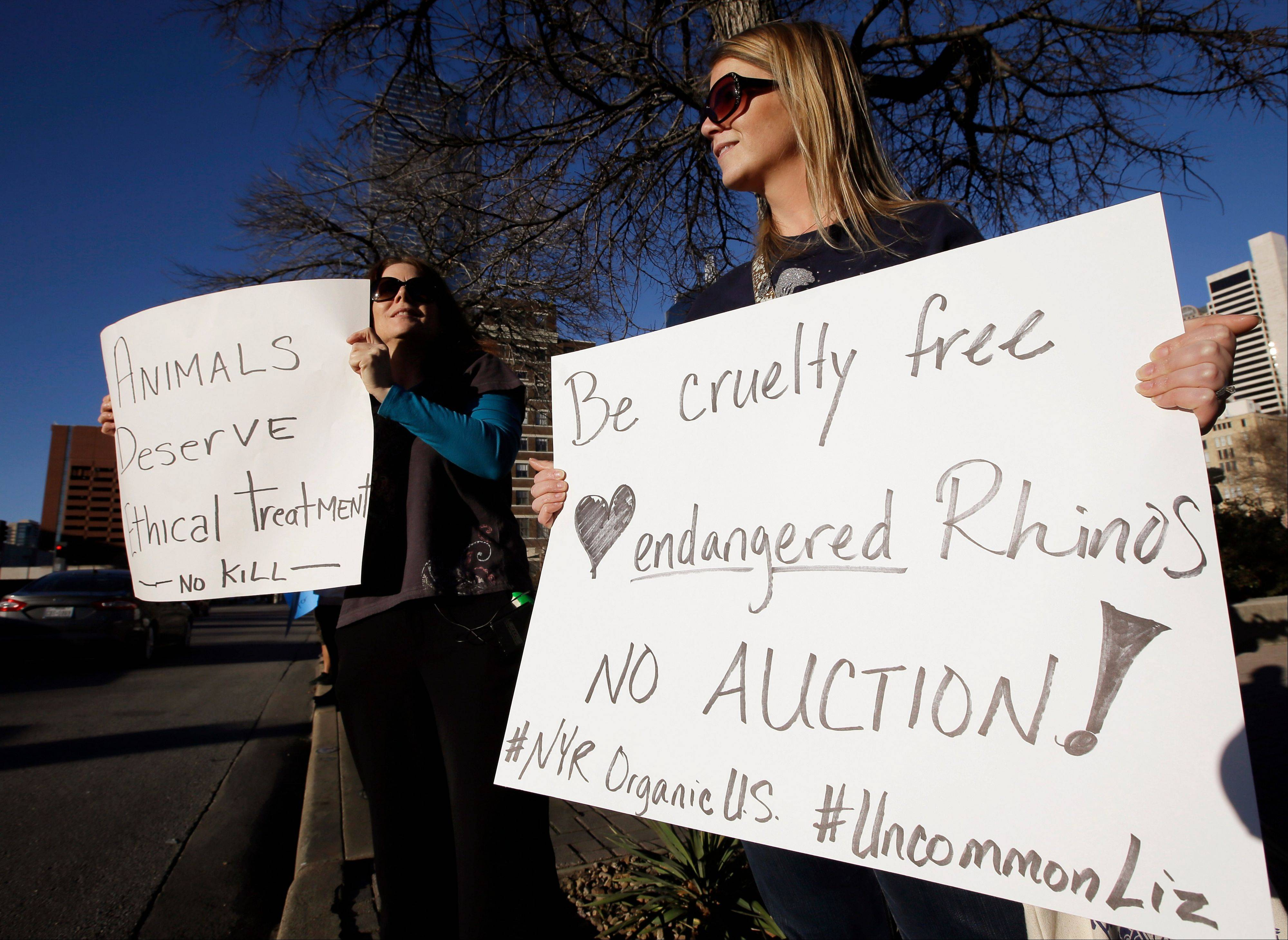 Sheila Jackson, left, and Liz Smith, both of Carrollton, Texas, hold signs Saturday as they protest outside the Dallas Convention Center where the Dallas Safari Club is holding its weekend show and auction.