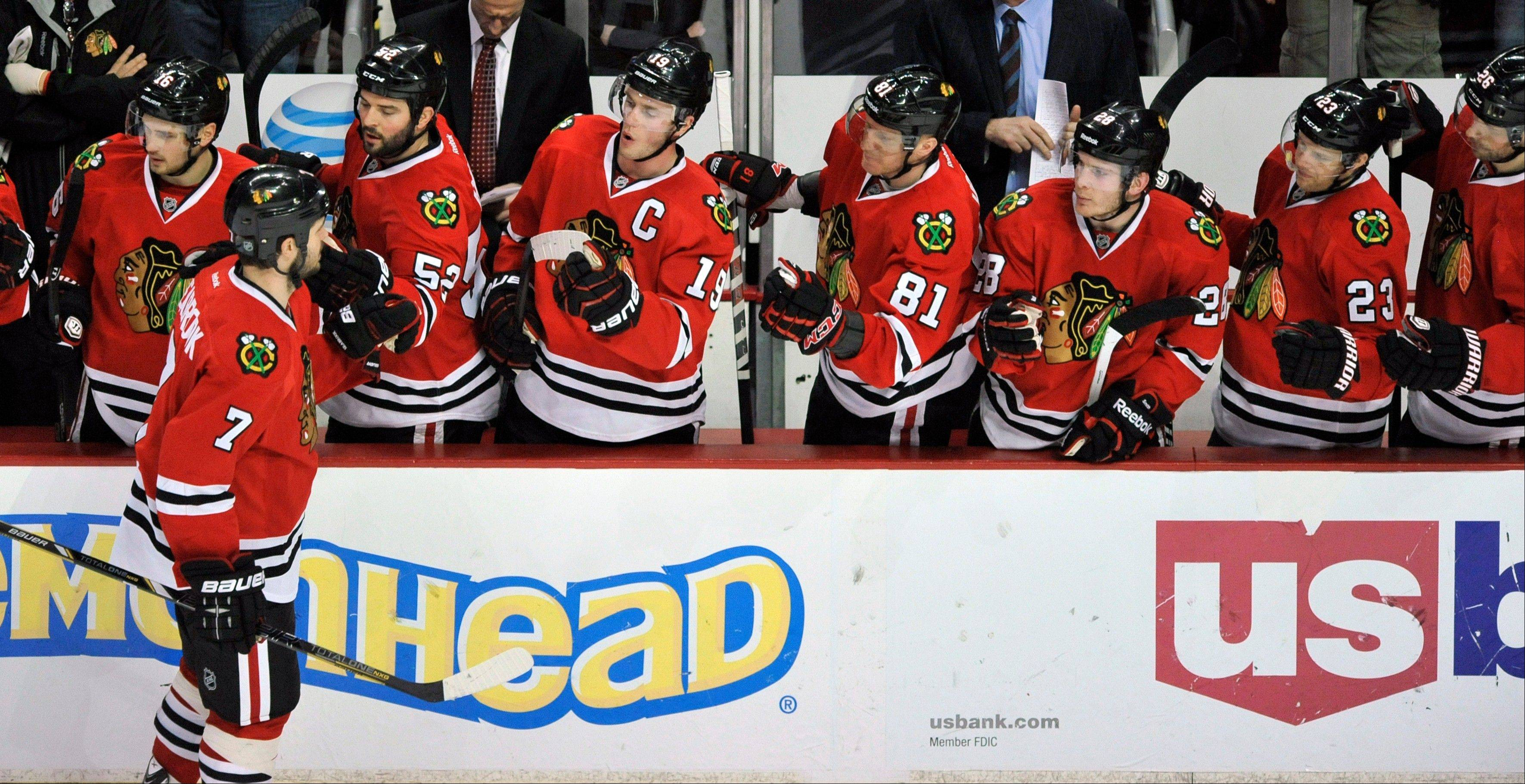 Brent Seabrook (7), celebrates with teammates after scoring a goal during the third period of an NHL hockey game against the Edmonton Oilers in Chicago, Sunday, Jan. 12, 2014. Chicago won 5-3.