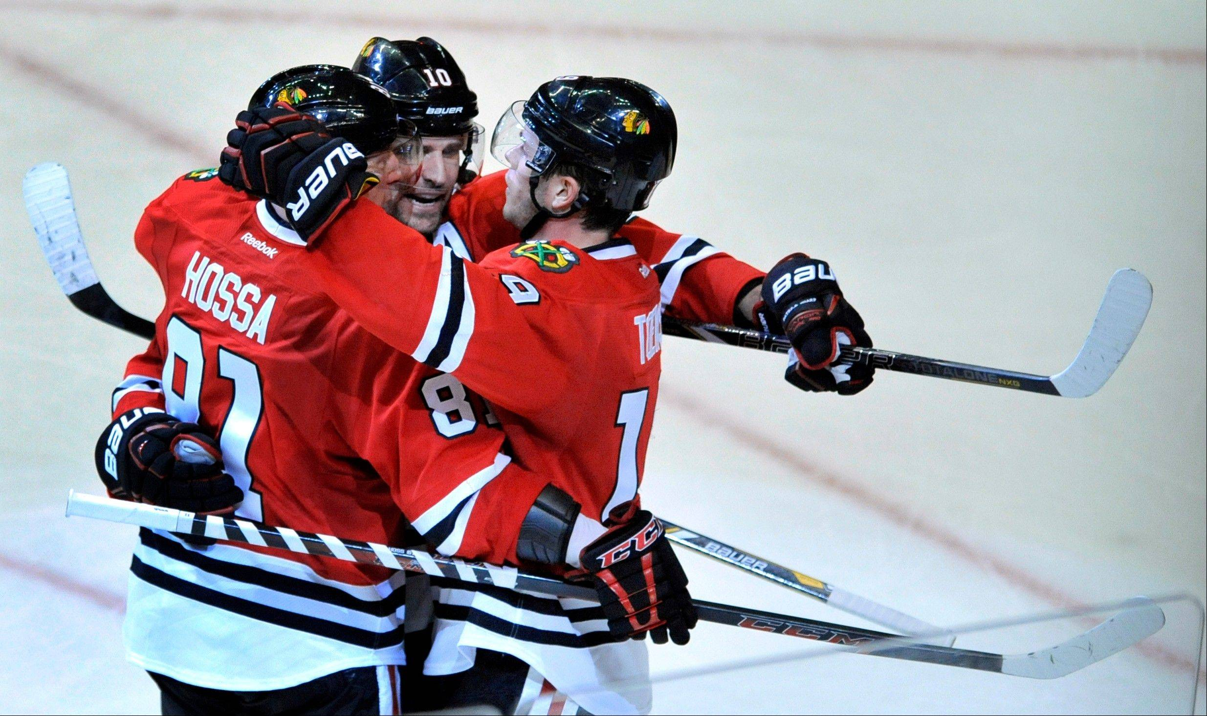 Chicago Blackhawks captain Jonathan Toews (19) celebrates with teammates Patrick Sharp (10) and Marian Hossa (81) after scoring a goal during the second period of an NHL hockey game against the Edmonton Oilers in Chicago, Sunday, Jan., 12, 2014.