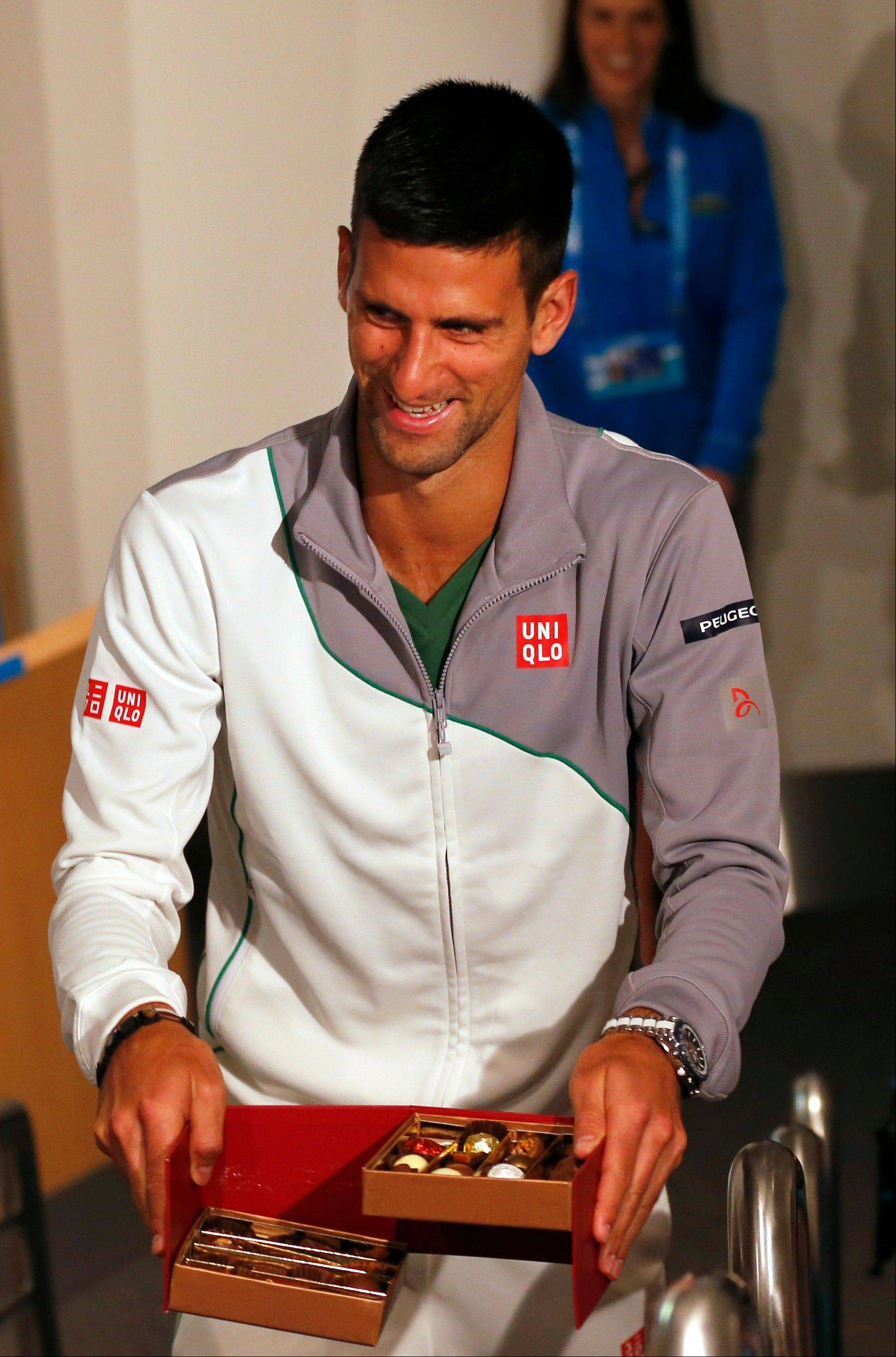 Novak Djokovic, who is seeking his fourth straight Australian Open tennis title, hands out chocolate to reporters during a news conference ahead of the championship tournament in Melbourne, Australia.
